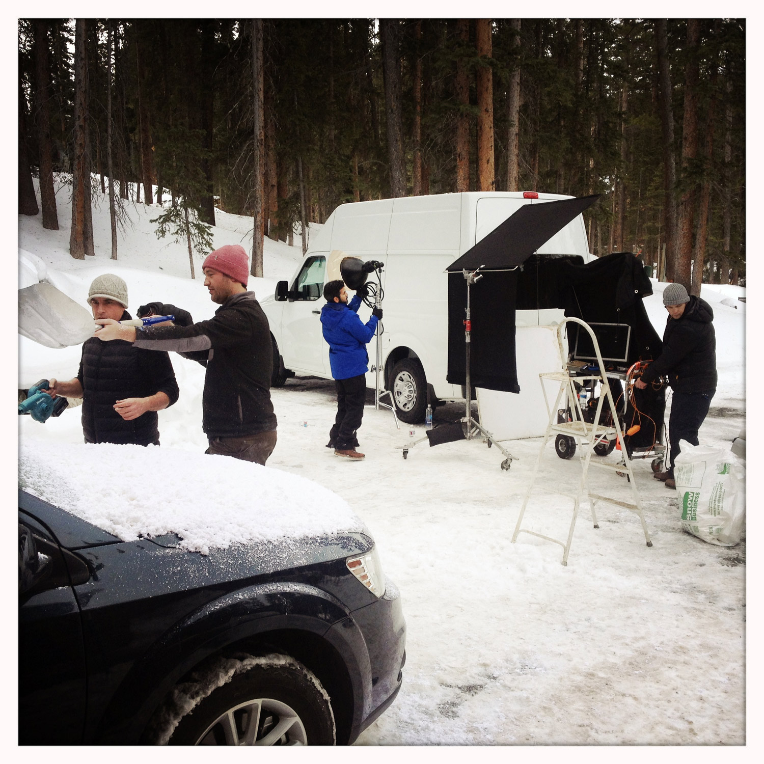 Prop stylist, Evan Madden (far left) adding snow to car.  Evan's represented by  Artist Untied .