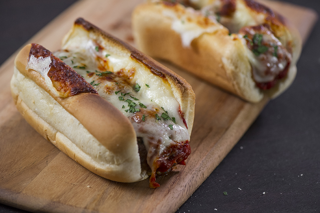 """1. Meatball Hero - It may say """"kaiser roll"""" on the label, but there's no restrictions on what you can put in 'em. These meatball heroes will showcase your creativity and turn you into a hero of your own—a tailgate hero—regardless of what happens on the field."""
