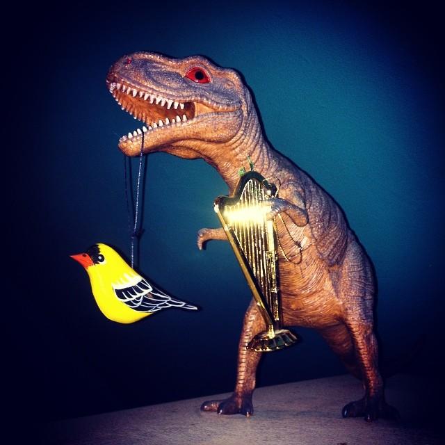 @angelaharrer assembles scenes on top of our fridge. Tonight T-Rex plays a golden harp and eats a bird.