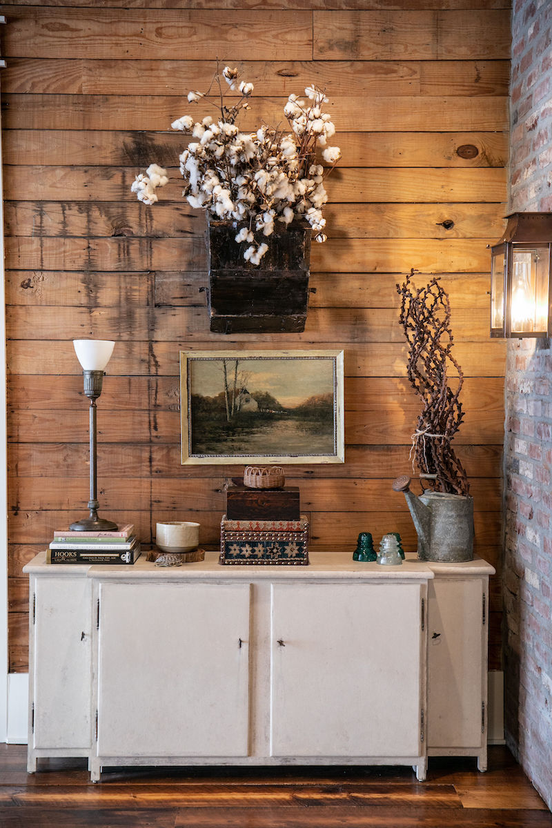 The home's original tongue-and-groove pine paneling creates a striking backdrop for this vignette.