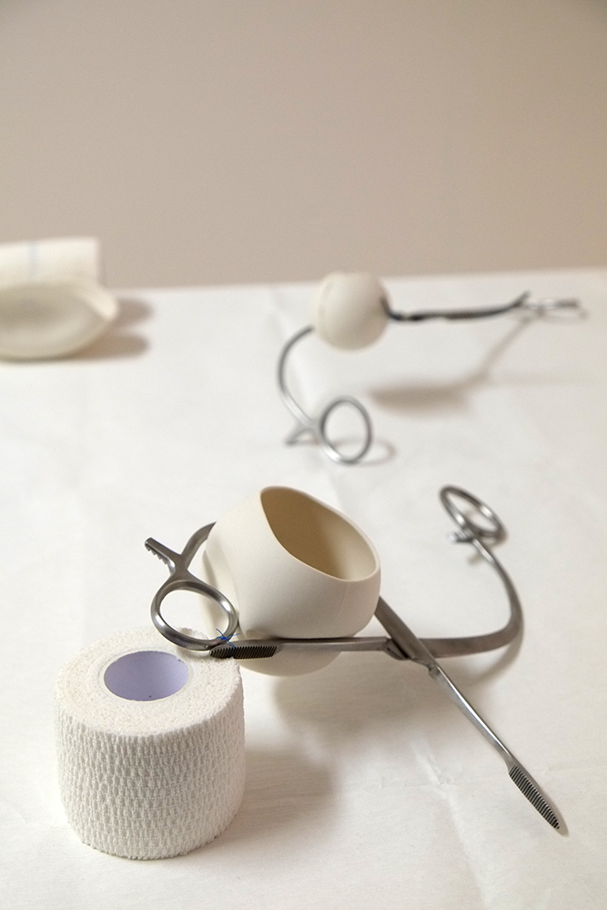 Porcelain, stainless steel surgical instrument, surgical sutures, bandage.  Approx. 25cm x 25cm x 15cm