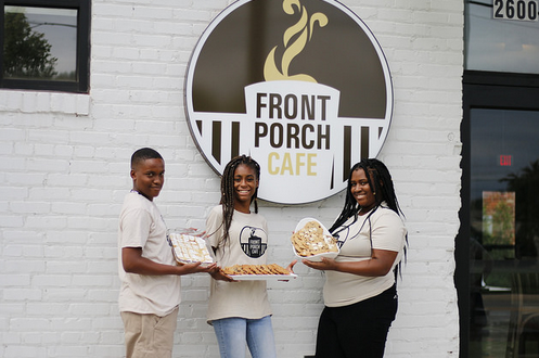 Jonathan, Tianna, and Altira show off tasty baked goods in front of the Front Porch Cafe.