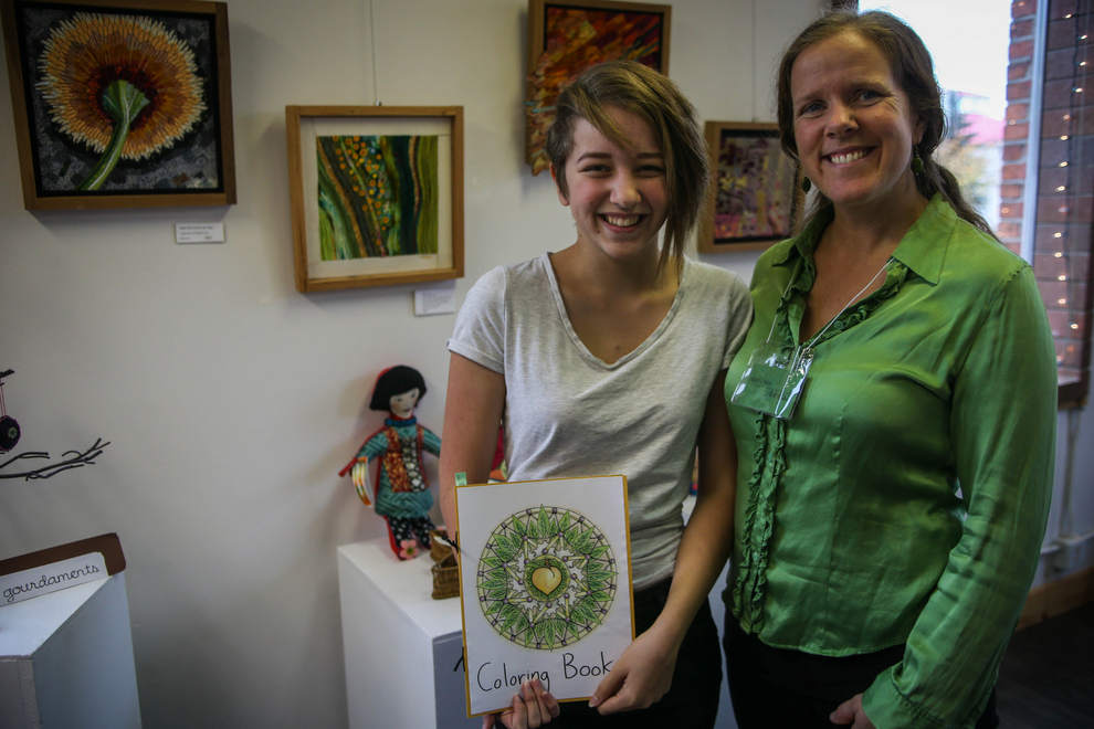 4/10 – Rimona Livie, 14, stands with mom and ArtChic, Mari, at the 11th annual ArtChics Art Sale and Benefit on Saturday at the Lincoln Art Gallery in downtown Eugene. Rimona designed and created coloring books for the sale, while Mari sold her fiber and ceramic artworks. (Mary Jane Schulte/The Register-Guard)