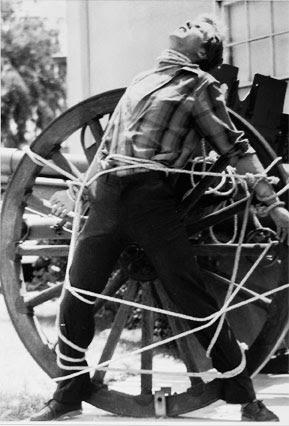[photo] Michael Griffin is the only 2-time winner of TV's World Magic Awards for Best Living Escape Artist, pictured during a heavy rope escape tied to an antique cannon wheel.