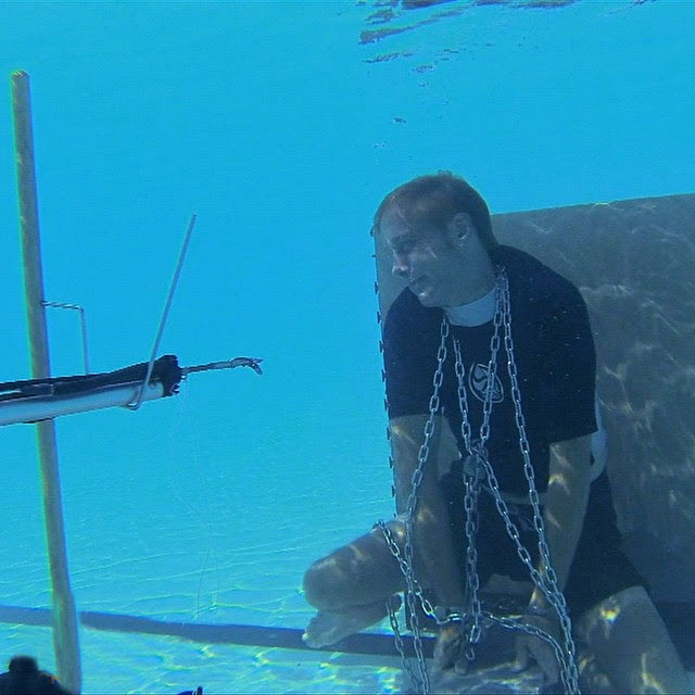 [photo] Best Living Escape Artist Michael Griffin pictured during an underwater escape for the TV show Extreme Escapes, a speargun aimed at his chest.