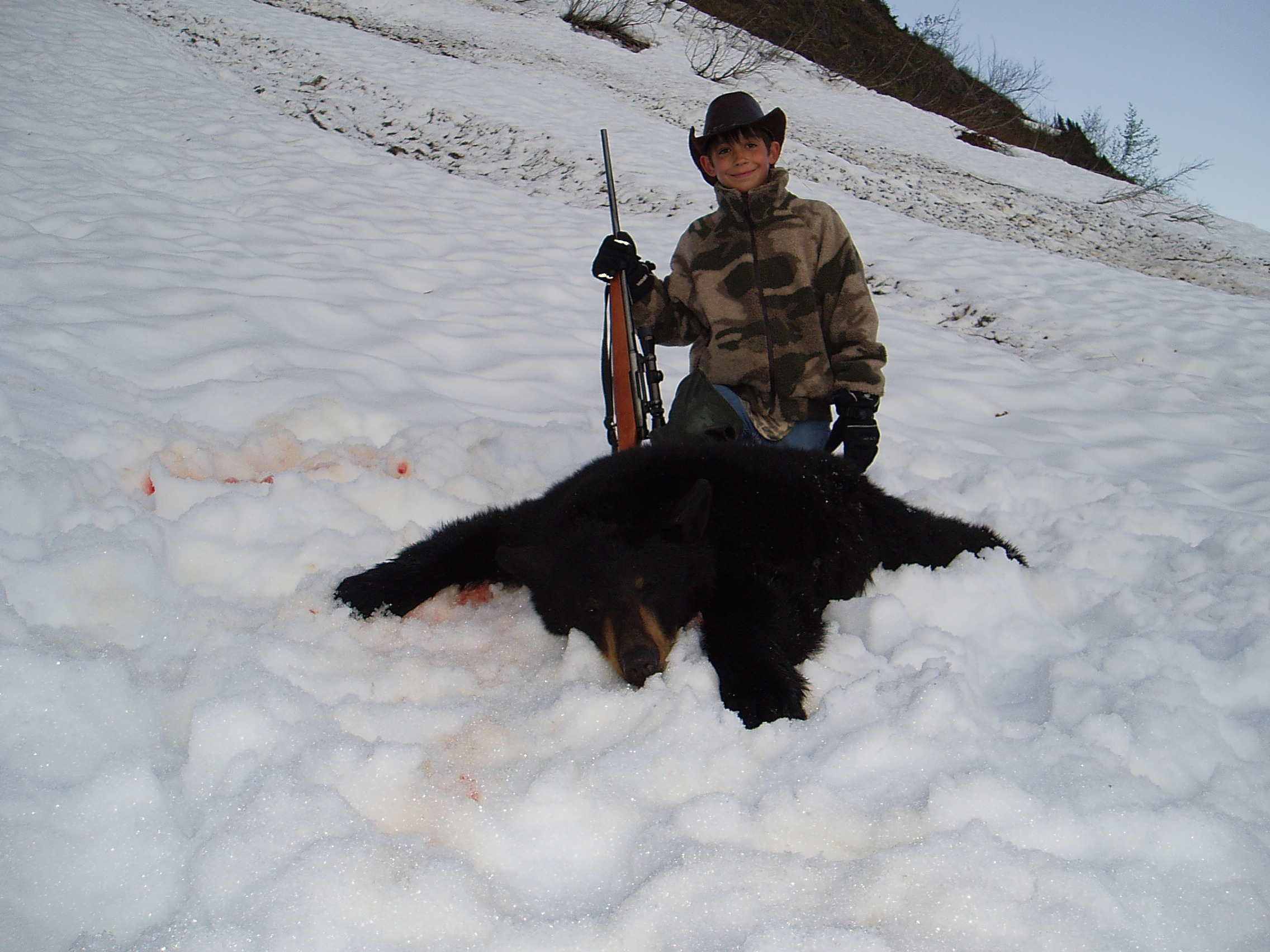 "Grandson Jared Juliussen 11 years old with his first black bear.  It took us two hunts to get his bear and it was a 5'7"".  Jared up-graded a few years later with a 6'5""."