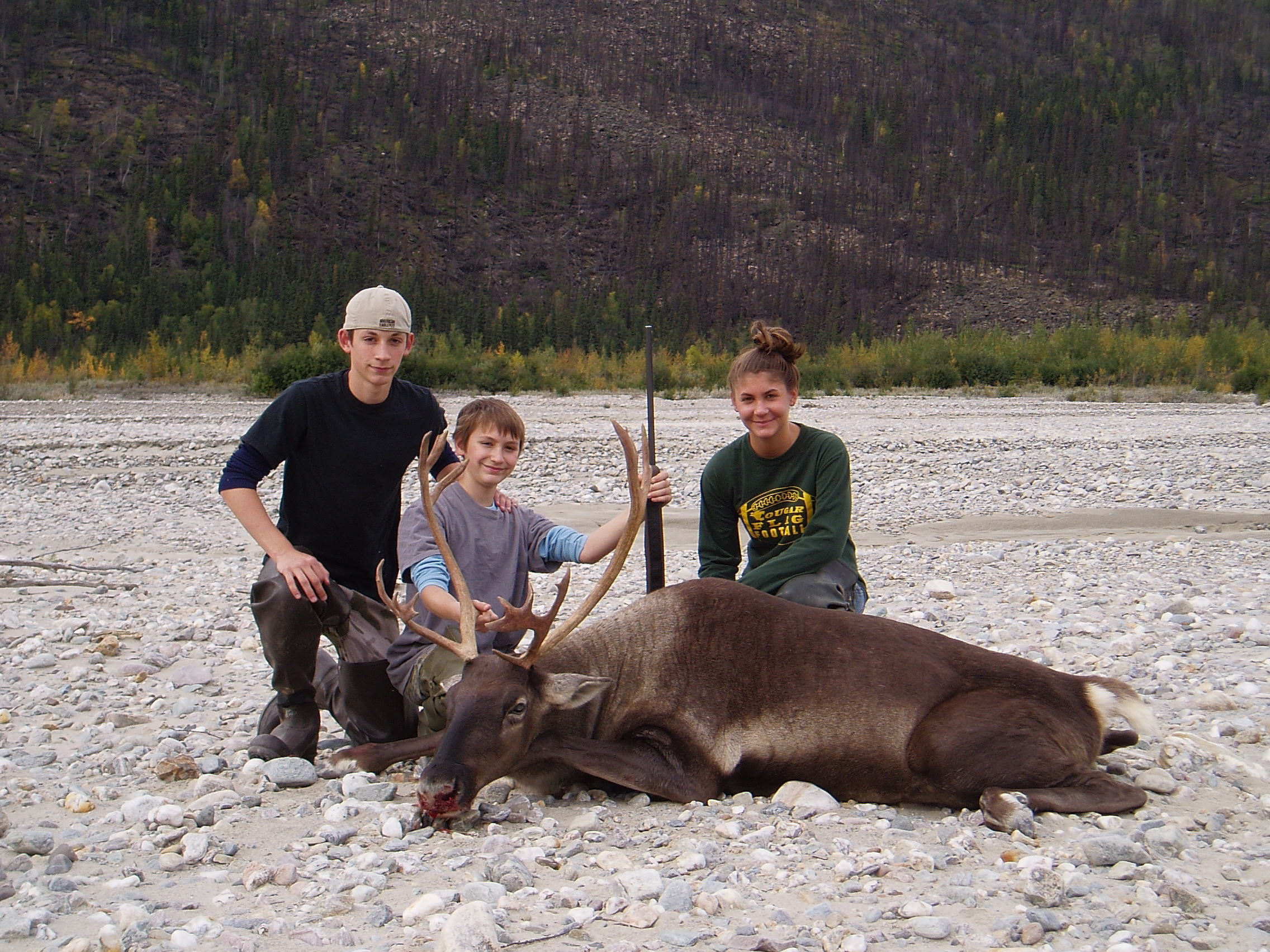 Nathan with his meat caribou surrounded by his brother Jared and sister Rachel.