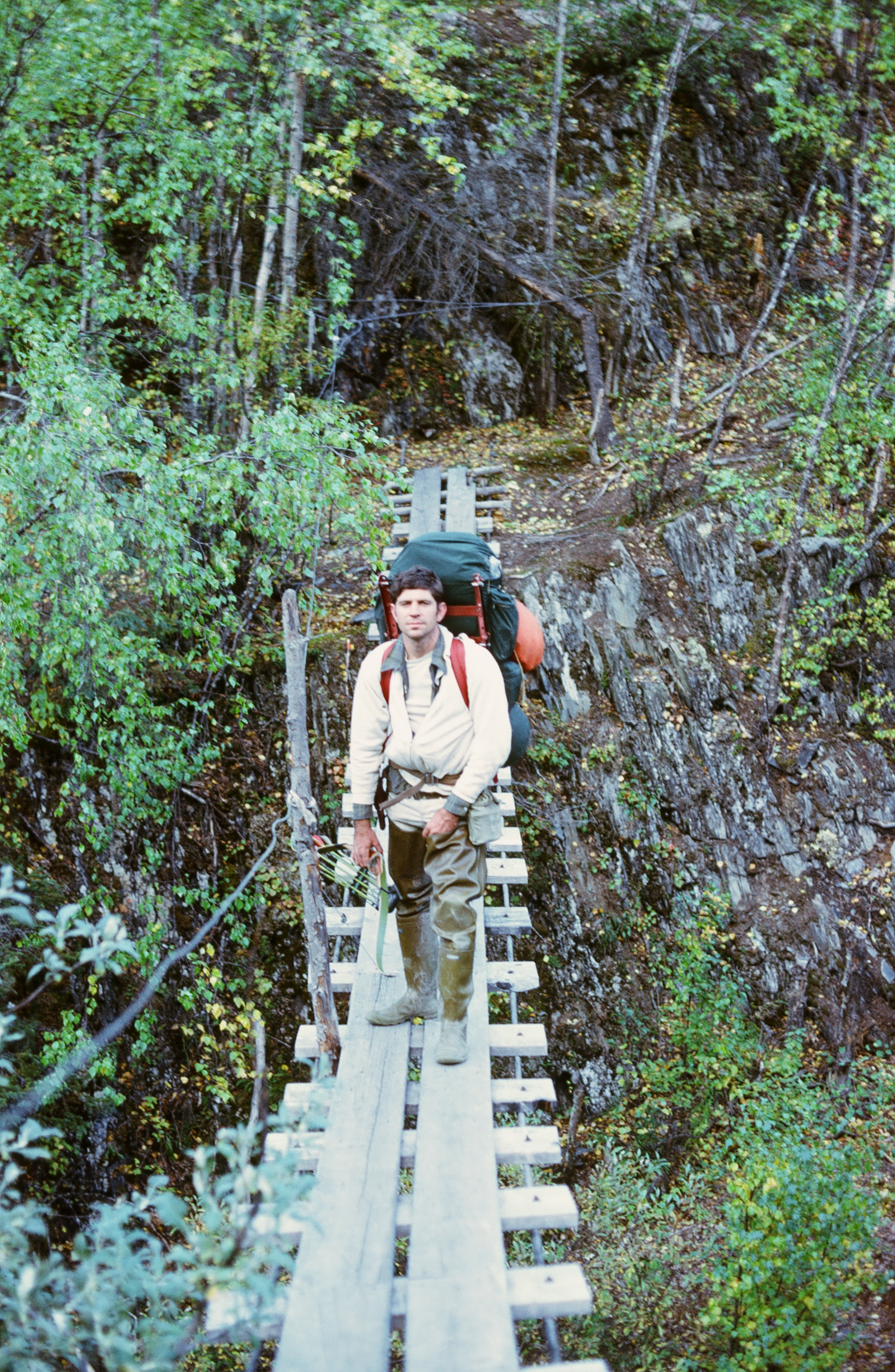 Me on the swinging bridge on a hunt in the early to mid 70's. One of the top cables is gone.