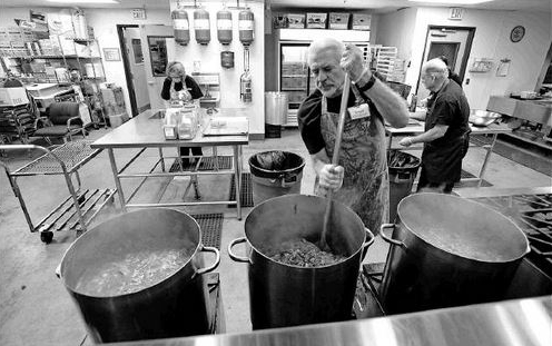 """I'm stirring the moose burger into the chili in one of the three 20 gallon pots. When I'm finished the chili will be about 1"""" from top of all three pots."""