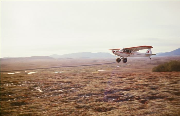 Me landing the cub at one of our mountain top camps. The flat top mountain you see in the background to the left is like the one I dropped Al and Steve off that overlooked the King Salmon River.
