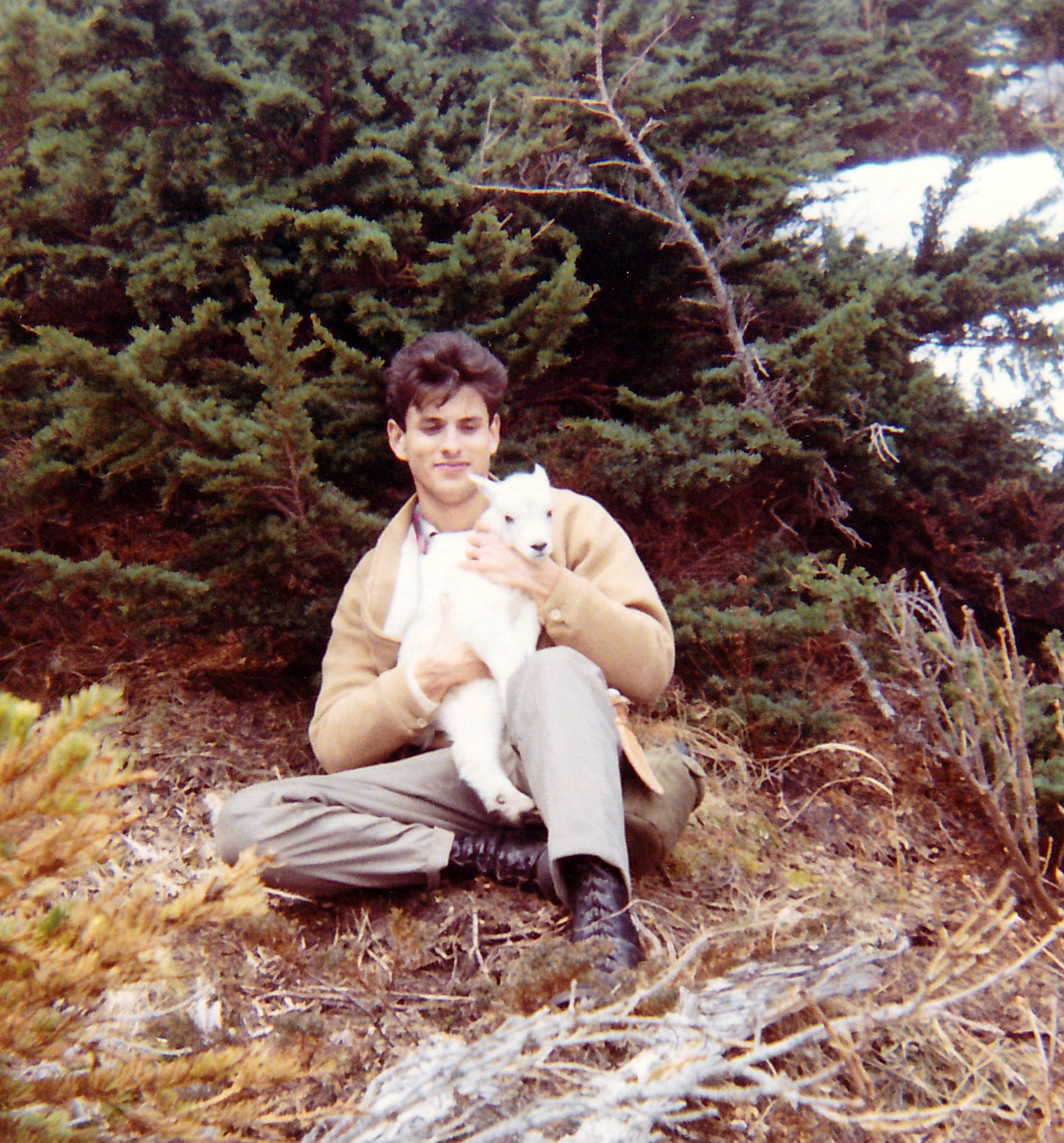 "Walter Burkett, a high school friend stationed at Elmendorf, with a ""kid"" goat.  We spotted a bear close to a nanny goat and made a stalk.  The bear got our wind and took off.  The nanny had hid her ""kid"" in the brush and as we came down the hill the ""kid"" came out."