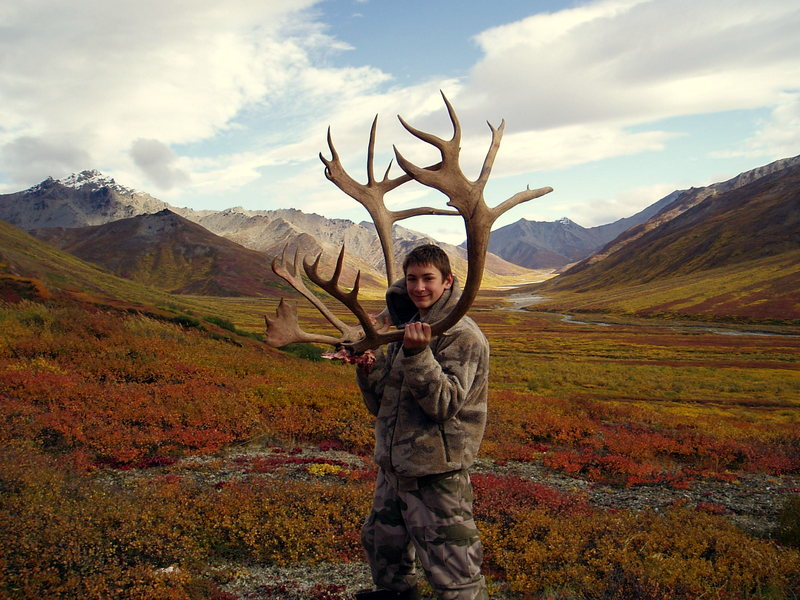 Nathan holding his antlers with all the beautiful fall colors in the background.