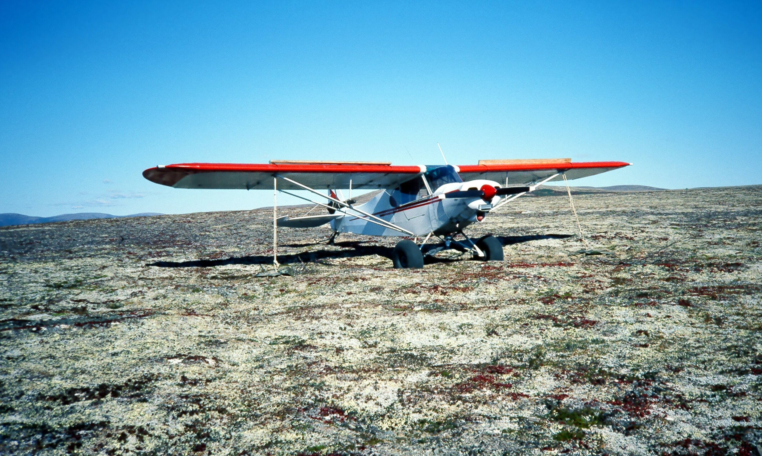 "I have 1936A tied down on a mountain top while hunting moose with Leonard Anderson in '87.  Tires are in a hole and I have 2x4's tied on the wings as ""wind spoilers.""  Hoping it won't get blown off the mountain."