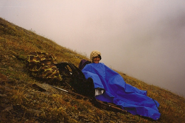 """My wife Karen, in 1998, waiting for the fog to lift. We had been sitting here for two hours. It rained and snowed. We were less than a 100 yards from the top of the ridge. There were two rams no more than 100 yards on the other side of the ridge with one of them right at 40"""". Because of all the nights that I had spent without my sleeping bag at about 6 P.M. I made the decision to pull off the mountain. About an hour later after we were on the bottom I looked back and the clouds had lifted and there laid the rams. I still think about that decision but if it had been the other way around I would have had another story about spending the night without our sleeping bags. It's all about time and distance."""