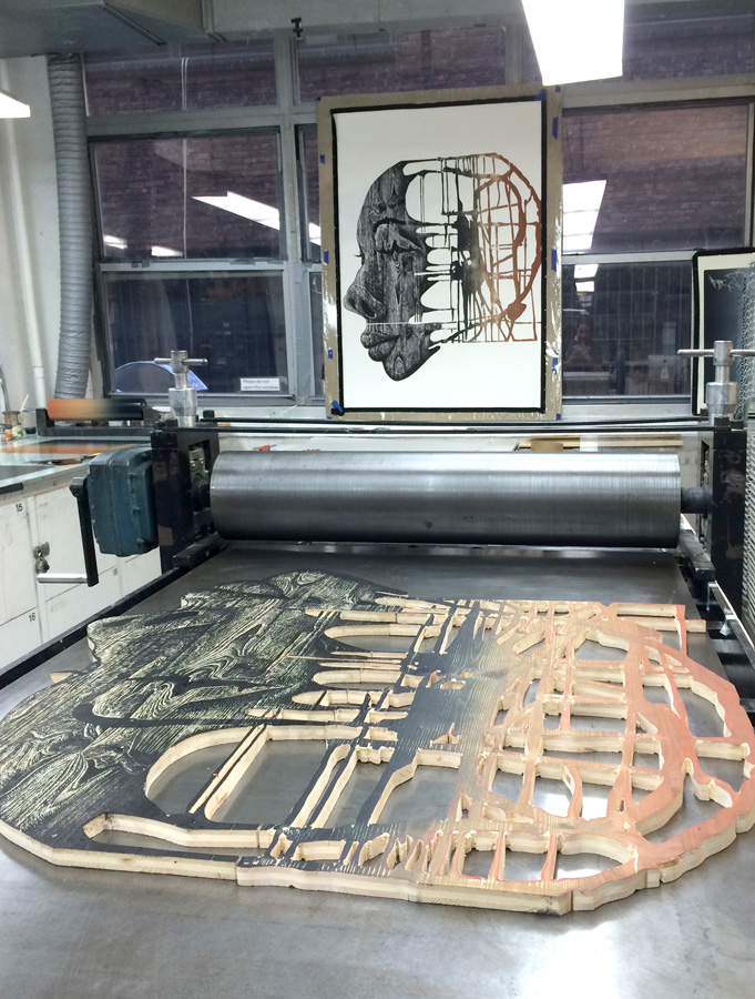 Carved woodblock using hand tools and a jigsaw being printed on an etching press at The Robert Blackburn Printmaking Workshop.