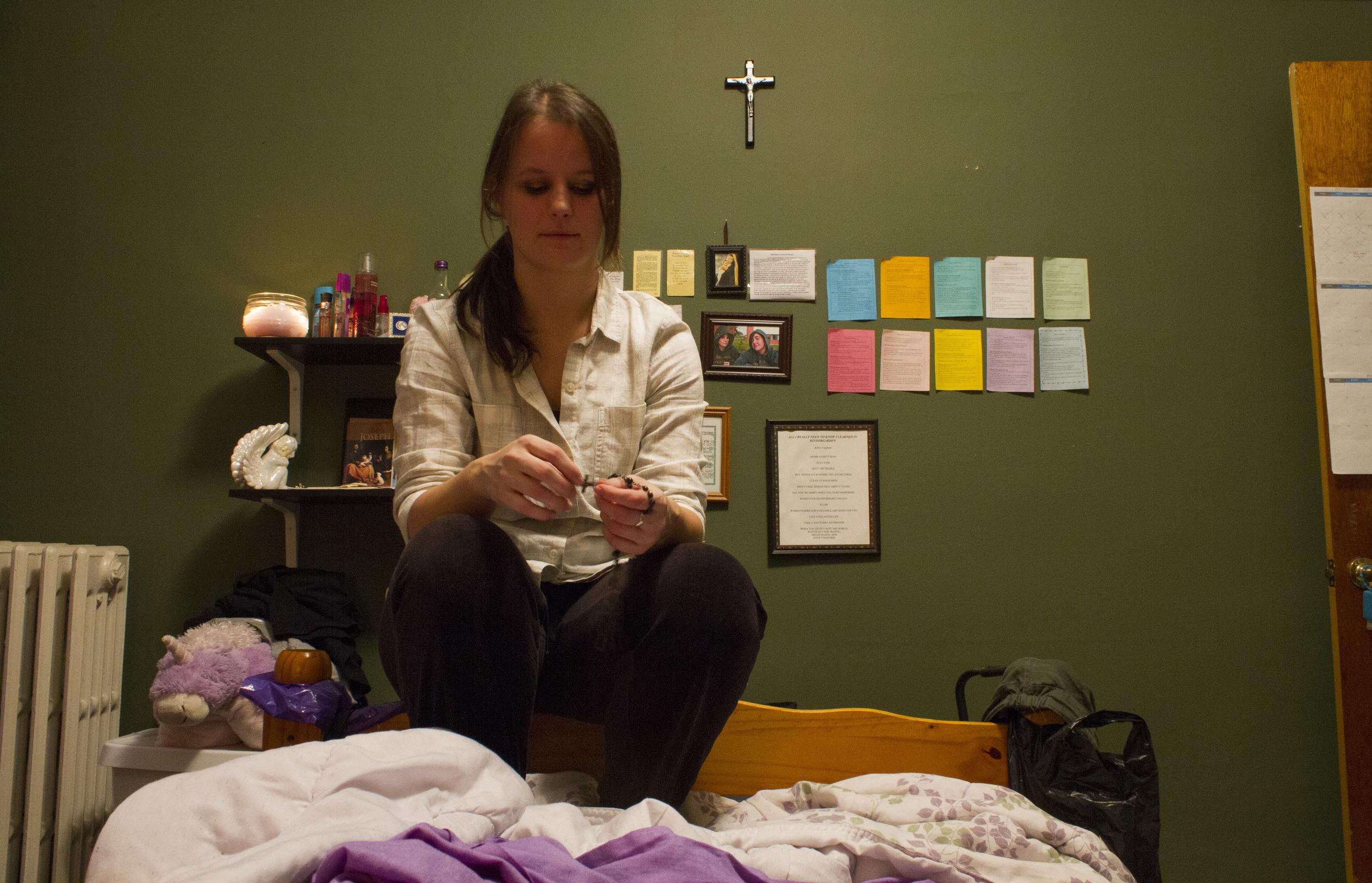 Catholic Minister Melissa McChesney, 24, holds rosary beads before evening prayers.