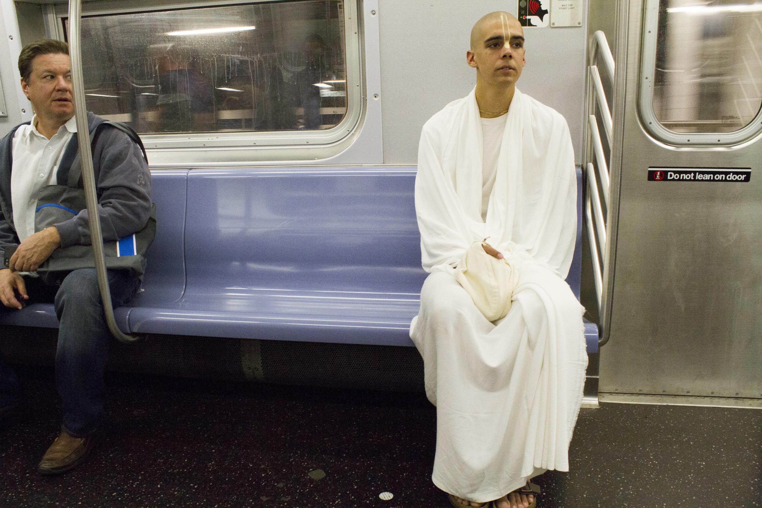 A train passenger checks out Hare Krishna monk Alex Seibel, 19.
