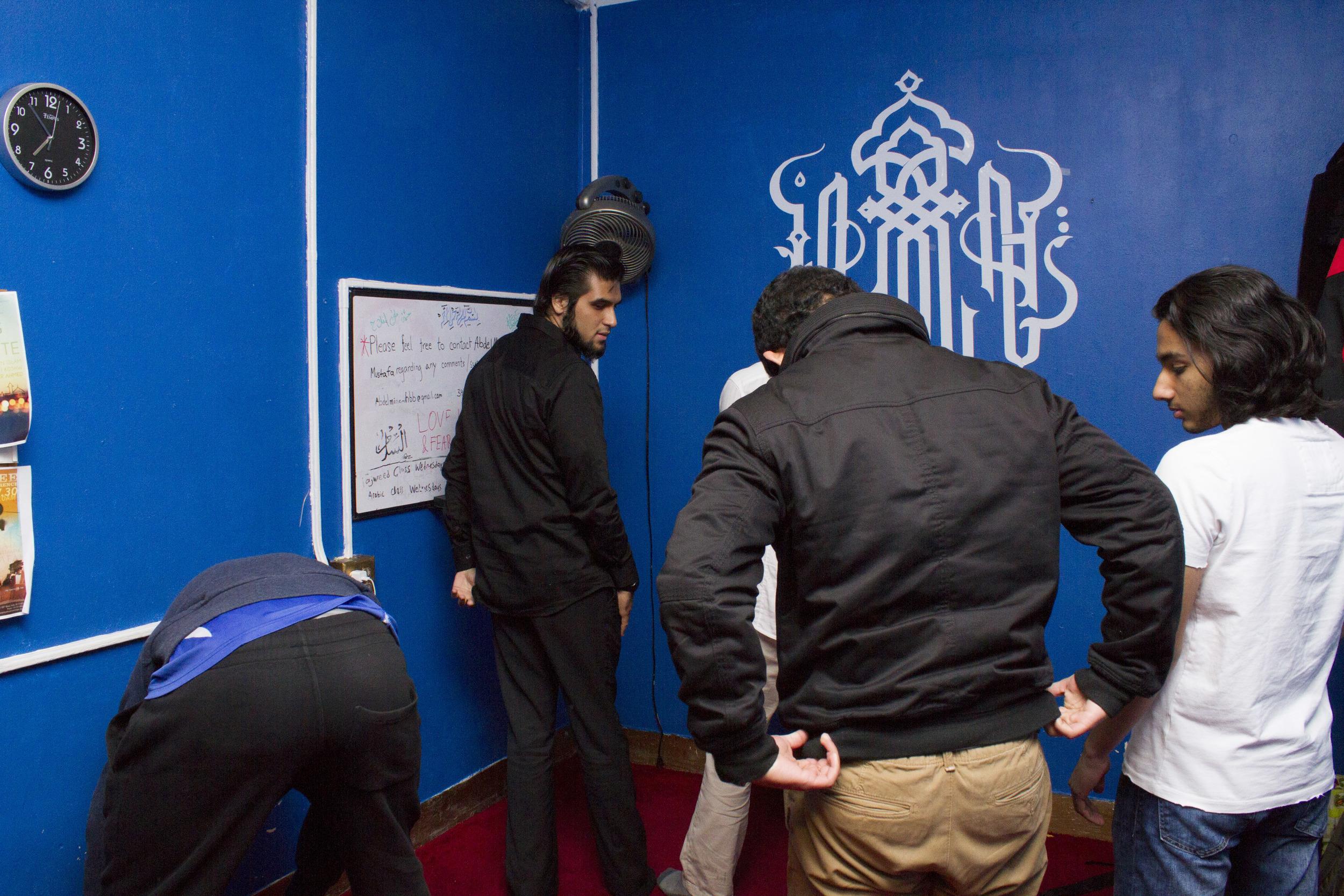 Navel Shah, 19, prays inside the school's Muslim prayer room.