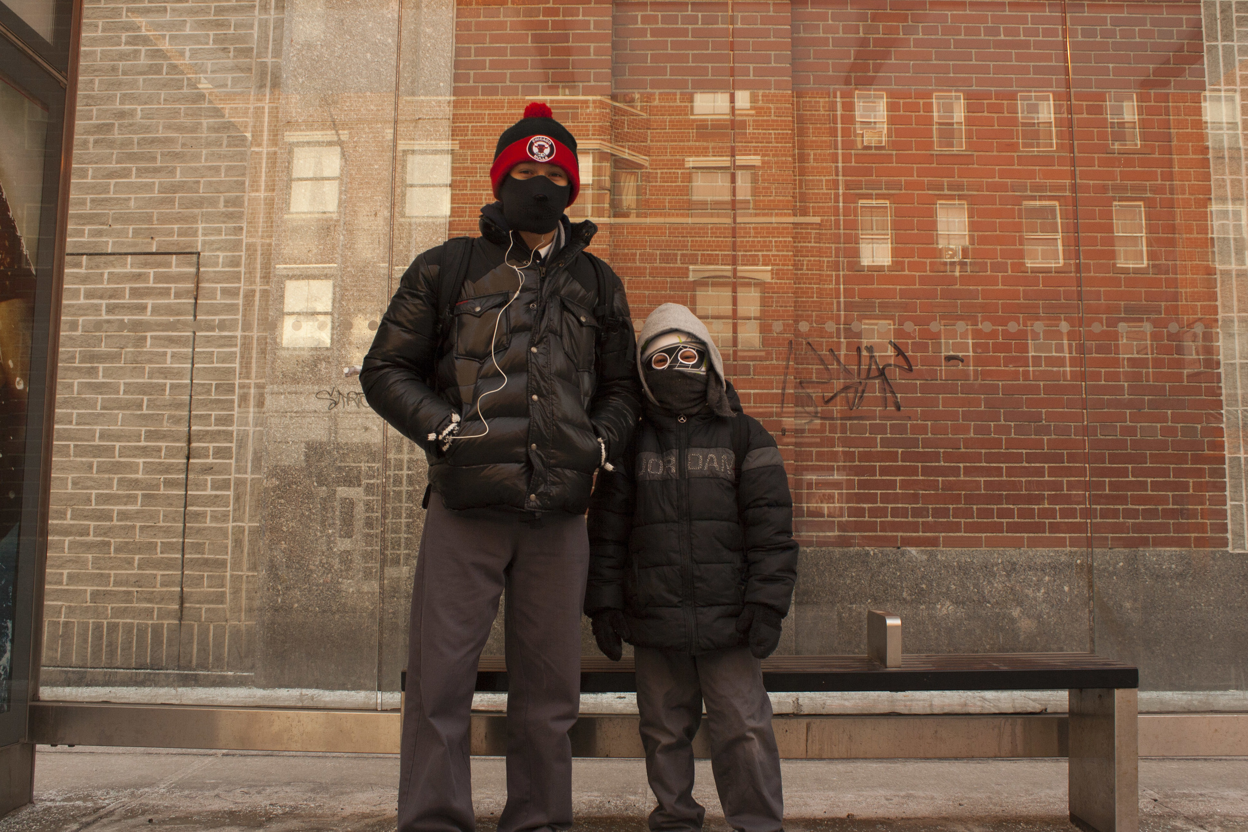 Brothers wait for the bus on a chilly winter morning.