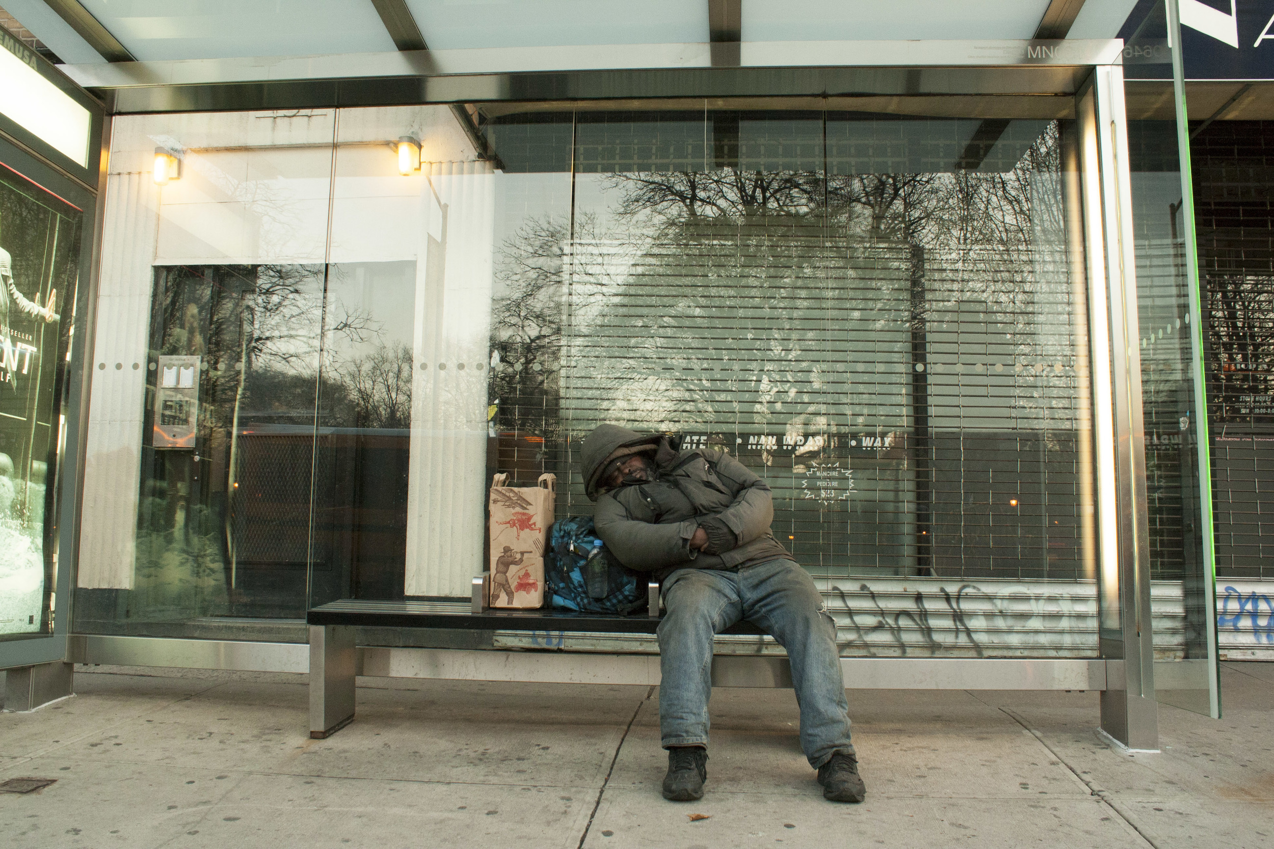 A man waits for the bus on Avenue A.