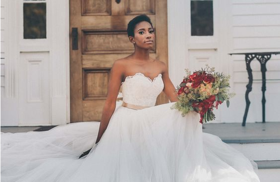 Bride in a lace & tulle ballroom gown sitting on steps.