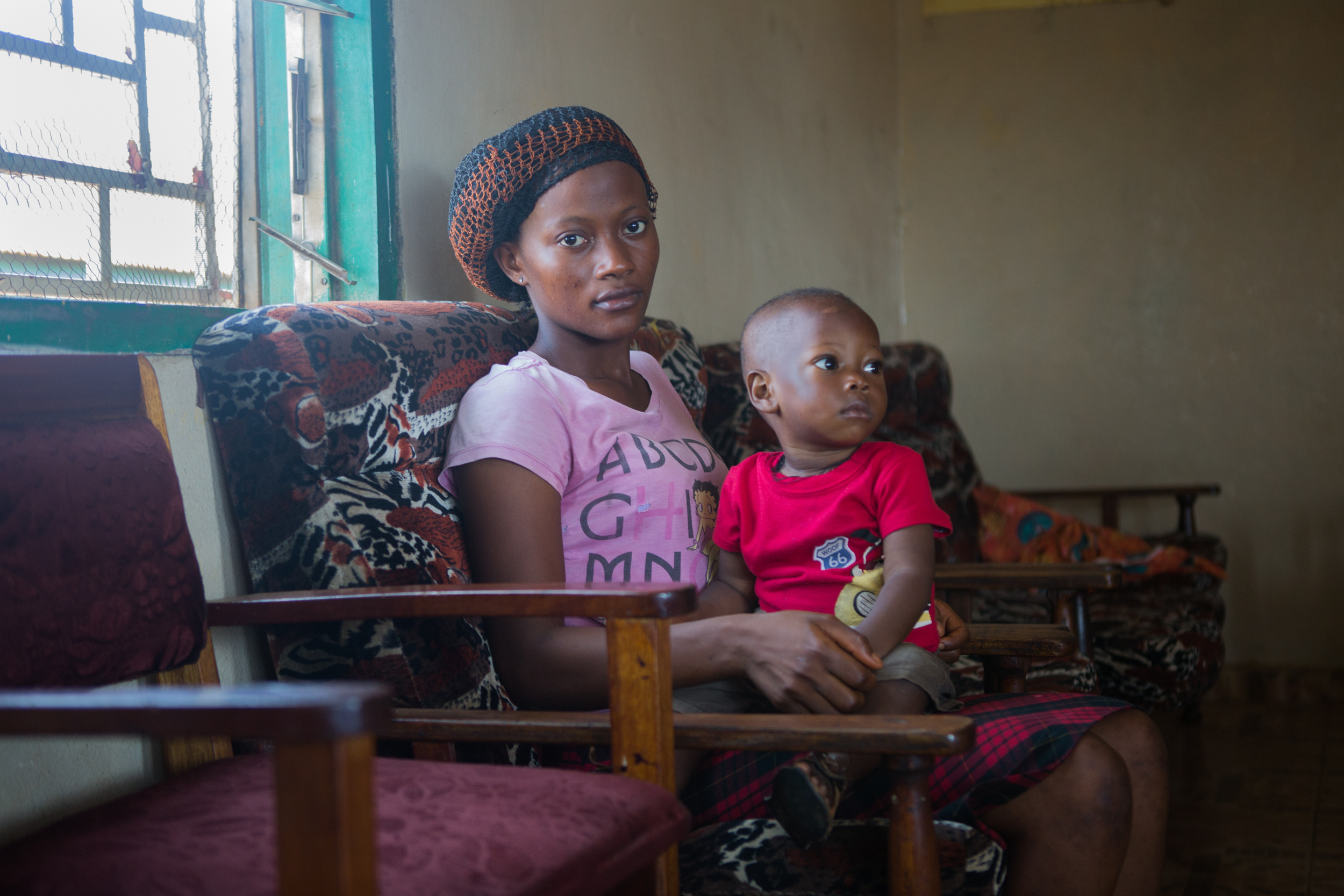 Alice, 18, and her son Mustafa, 1, sit in the waiting room before going to meet a social worker in Kissy, Sierra Leone on April 26, 2016. Alice's whole family perished during the Ebola Crisis in Sierra Leone in 2014, and around the same time she met a man who later abandoned her when she became pregnant. Since he left, she has abandoned her schooling and supports herself and her baby through odd jobs.
