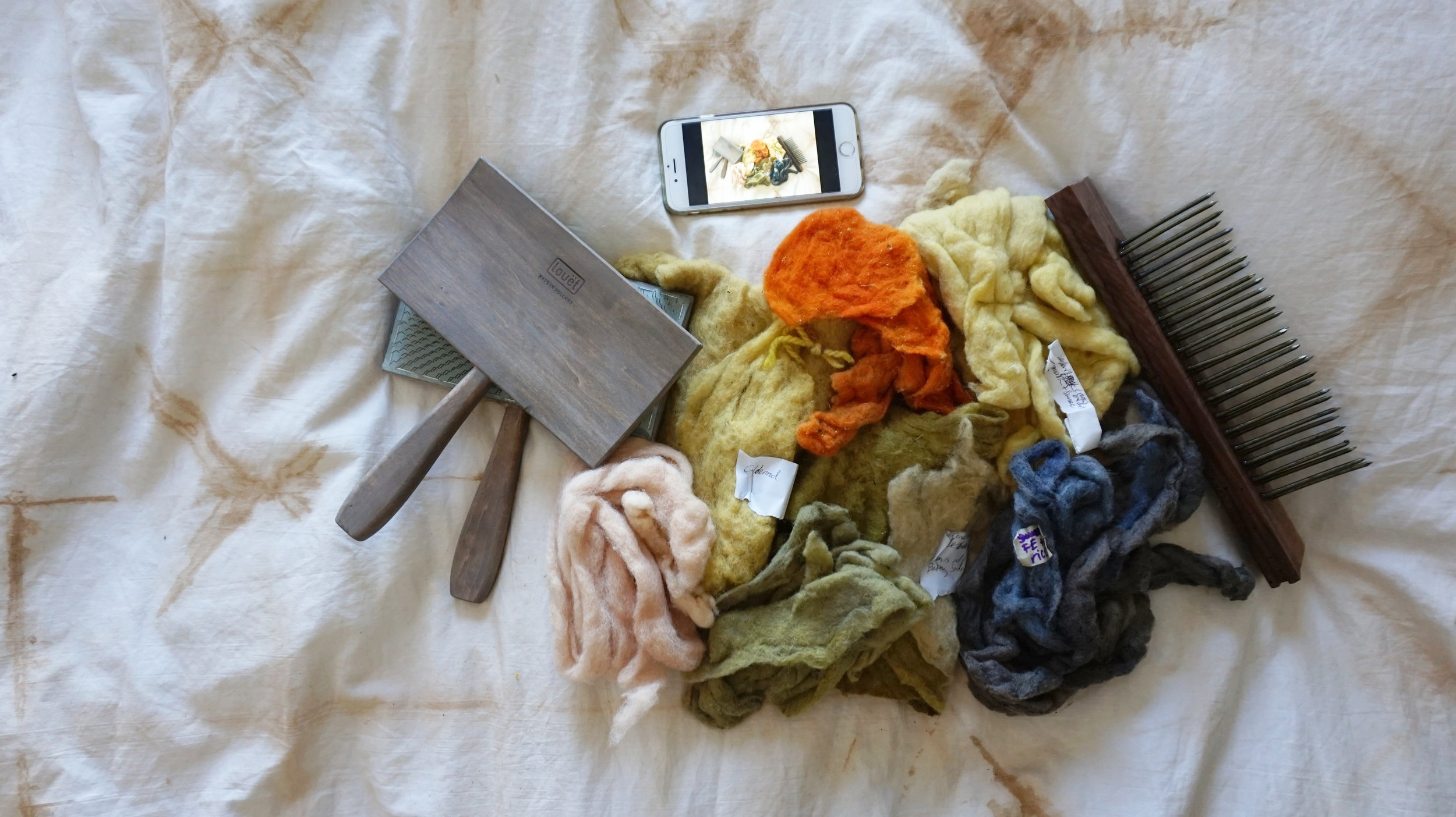 After 6 months of thorough lightfast testing (sunlight) and wash testing (good old-fashioned water and castille soap), the next step is carding or brushing the dyed batts and blending them. Monarda or Bee balm (otherwise known as the bergamot in Earl Grey) is featured as the pink and also some green in the middle; Coneflower (known as echinacea) also in lovely leaf greens; brilliant orange from Coreopsis (also called tickseed); goldenrod that stays as lovely in the dyepot as it does in nature; and Forbidden Rice is that dastardly gorgeous blue. The Kevin McCallister type tool (far right) is a hackle which helps align and direct the fibers once fluffed. I made this tool with a precise drill press in reclaimed walnut flooring although fibers really aren't that picky and you can certainly drill by hand. This is shot on a duvet shibori dyed with peony flowers of handsewn vintage linens.