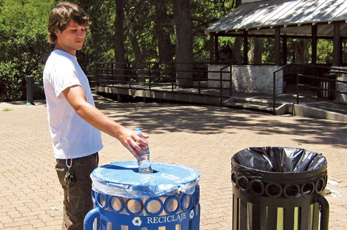 A park patron drops a plastic bottle into a recycling bin. Photo Courtesy of San Antonio Parks and Recreation Department