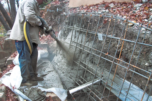 In areas where the bag walls were removed, the slope was stabilized with gunnite and piers. Note the wrapped drain pipe and PVC weep. Photo Courtesy of Hasen Construction