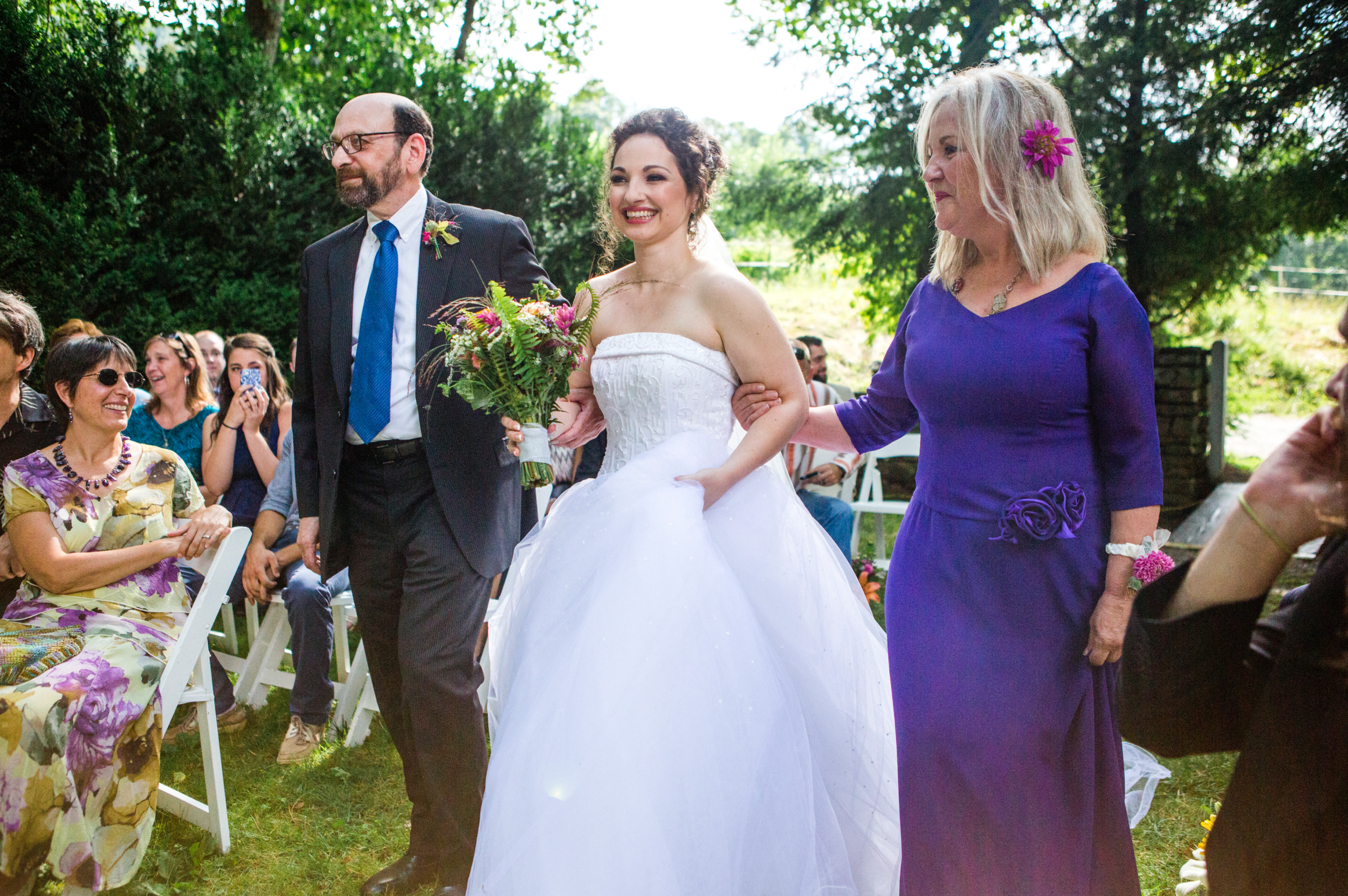 Delighted bride Walking down the aisle with mom and dad