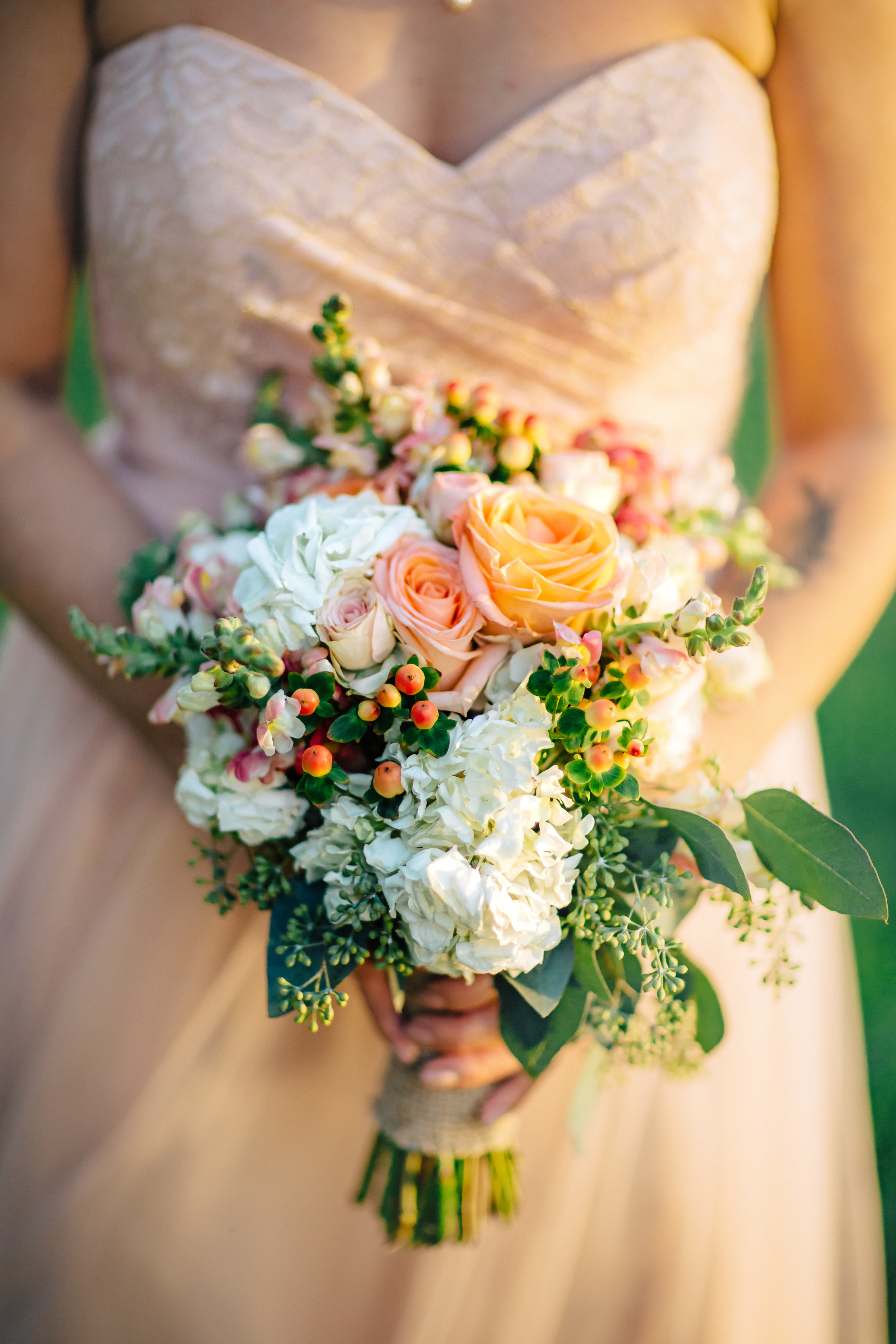 Langford Park wedding, with a floral bouquet inspired by peach, salmon, white, and soft greens, wrapped in rustic burlap.