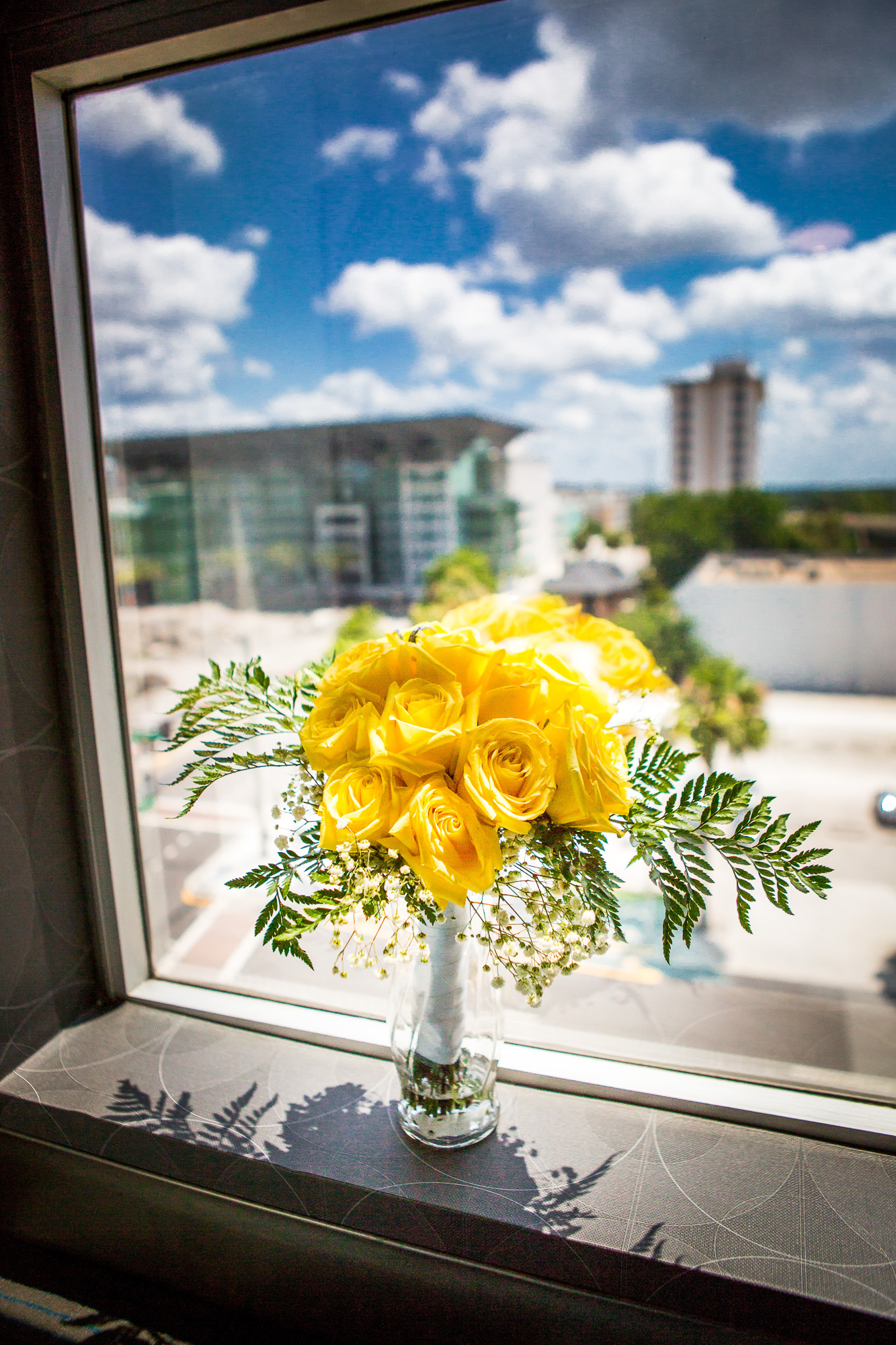 Yellow rose bouquet, with baby's breath and ferns, wrapped in white satin for this Orlando bride.