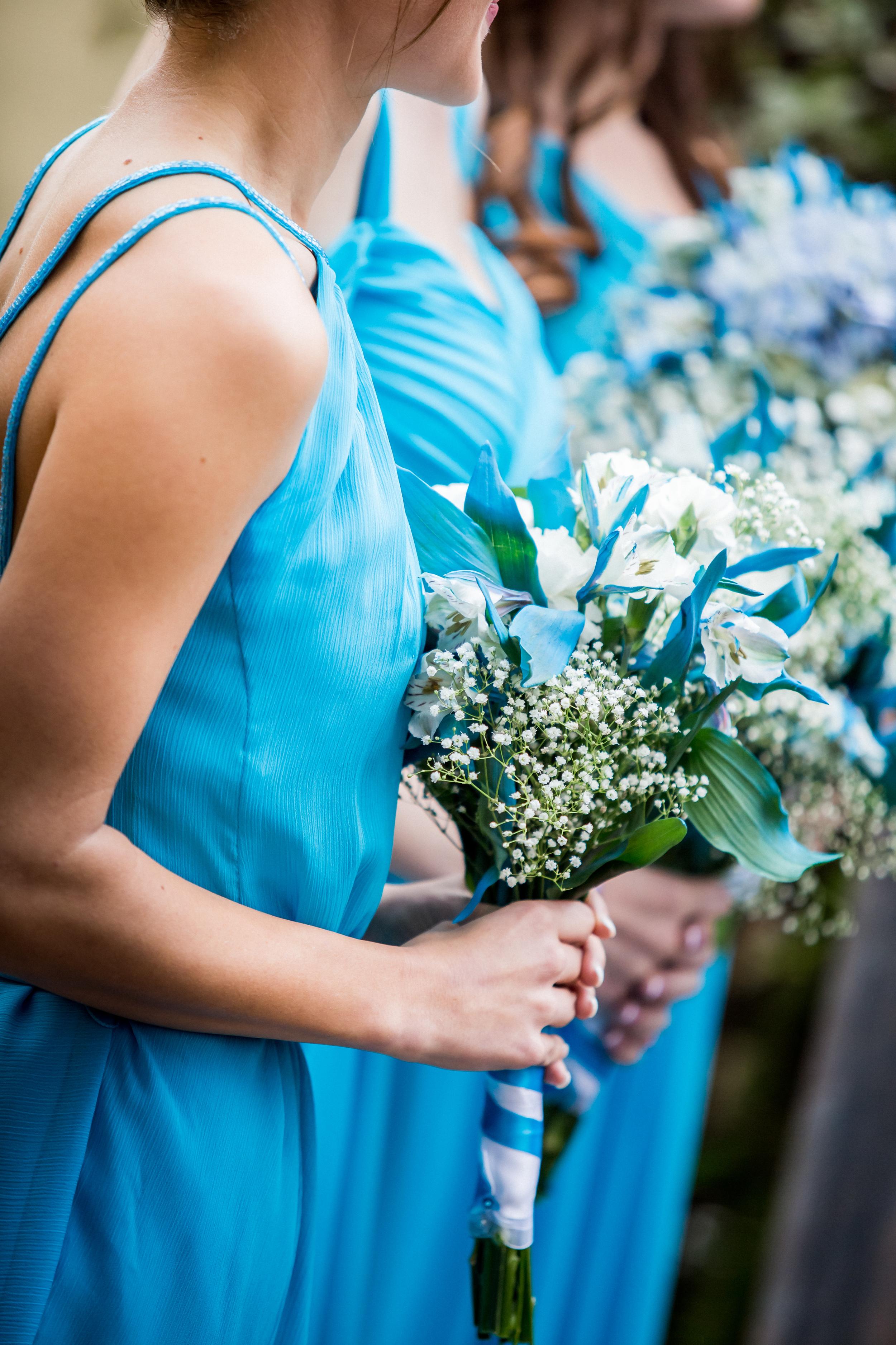 Sky blue wedding bouquet, with white alstromerias, baby's breath, and blue flower petals.