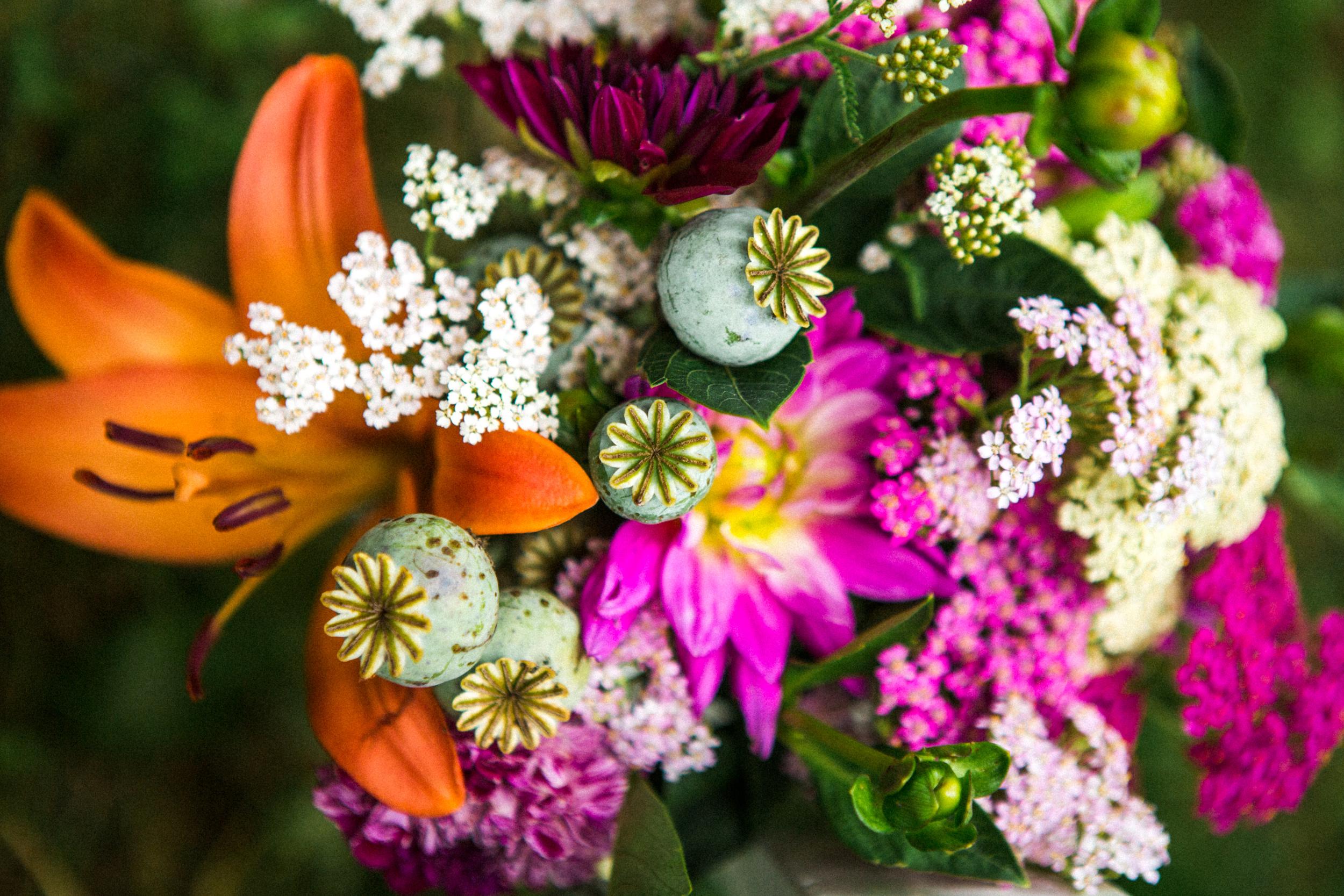 Rustic garden bouquet of poppy seeds, orange lilies, fuschia flox and white flowers.