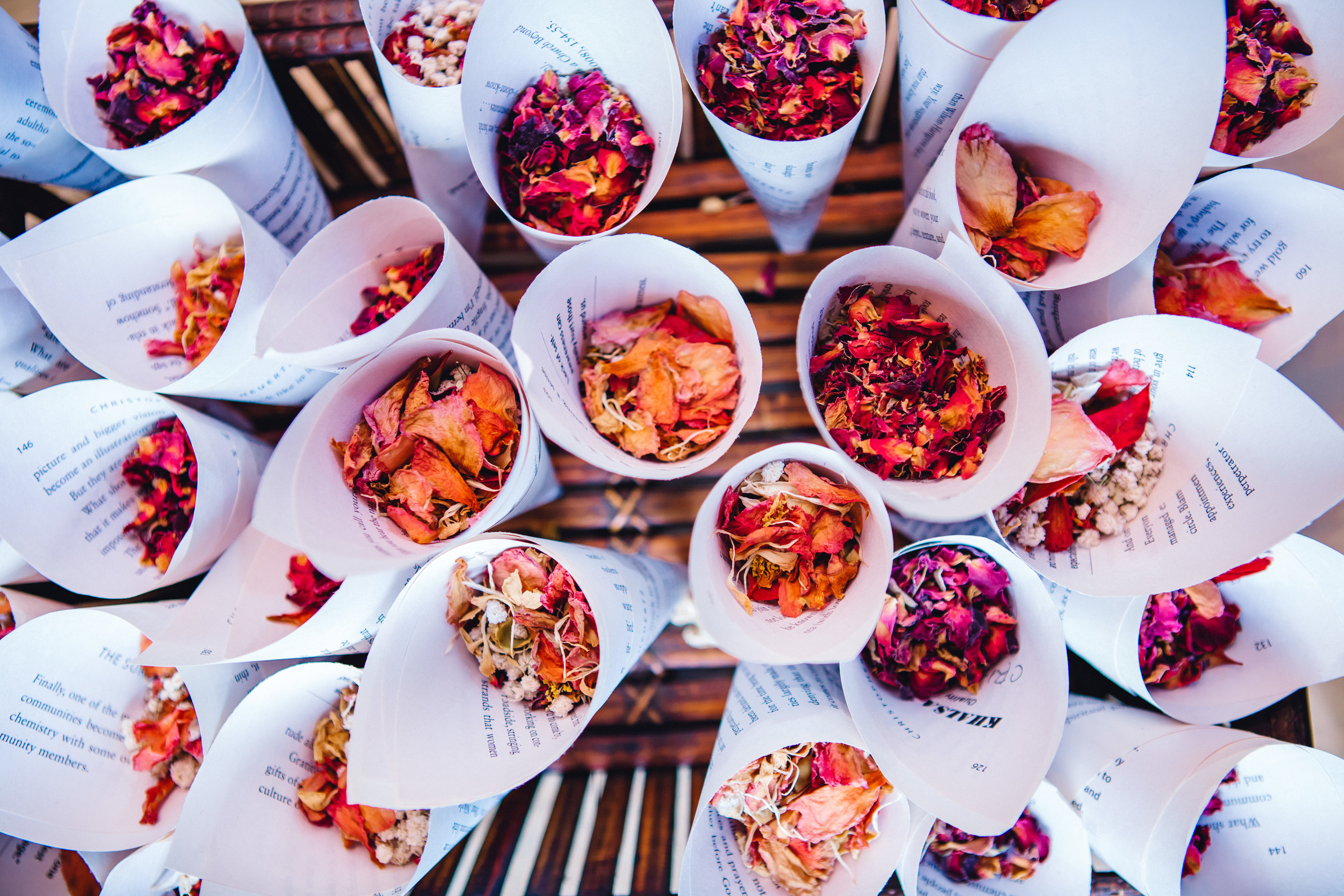 Book page cones with dried roses for guests to toss during the wedding exit.