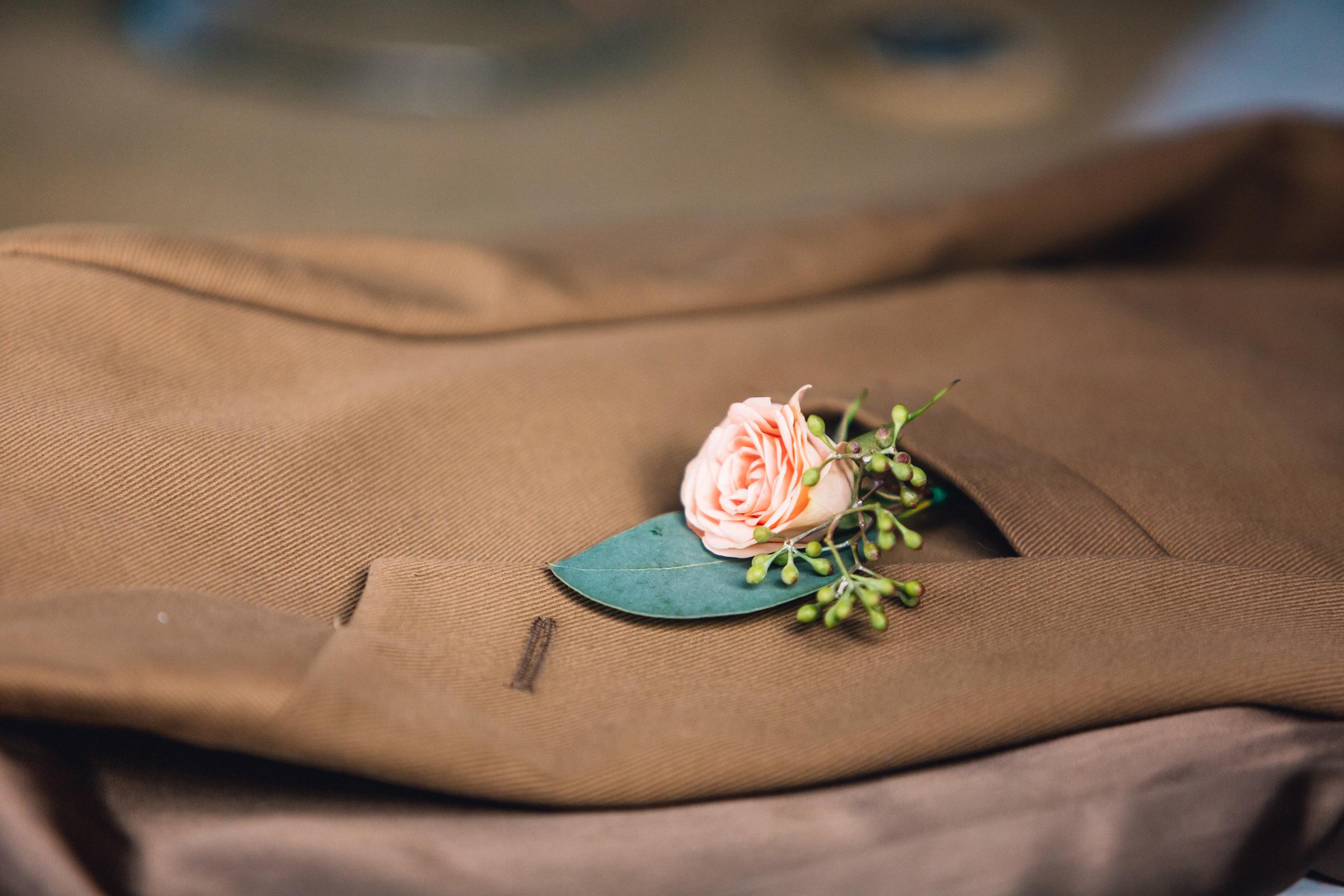 Pink rose and eucalyptus leaf groom boutinierre