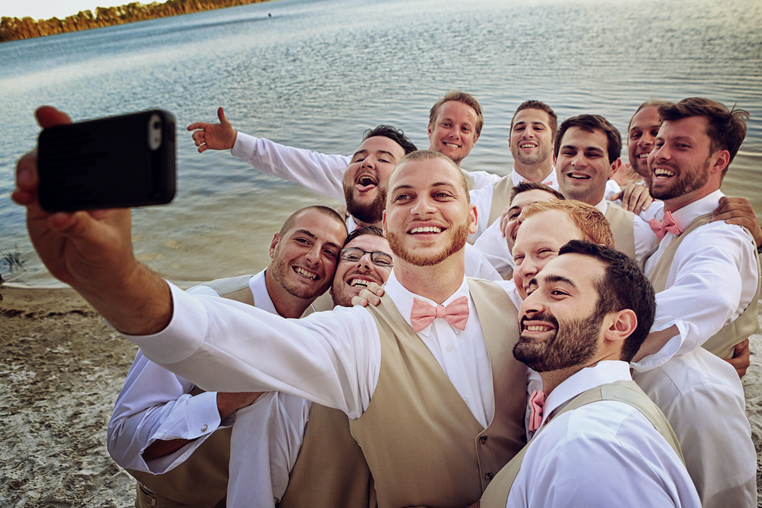 Funny groomsmen selfie in pink bowties at a Paradise Cove wedding in Orlando