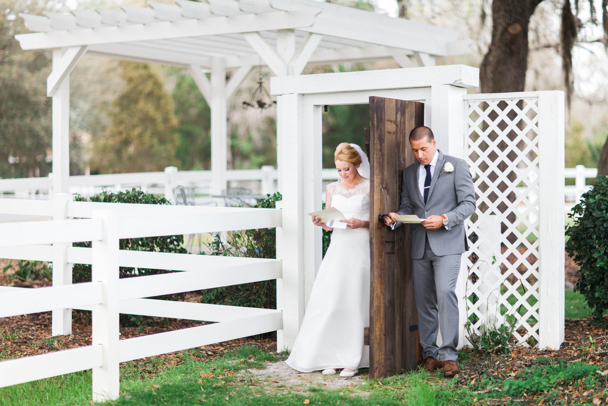 Bride & Groom exchange letters without seeing eachother around an outdoor doorway at their Bramble Tree Estate wedding