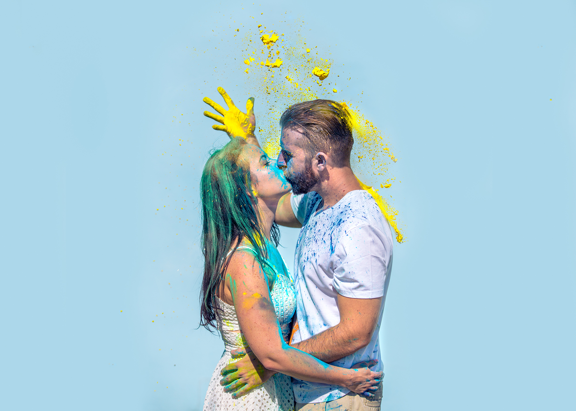 yellow holi powder engagement photos couple by a blue wall