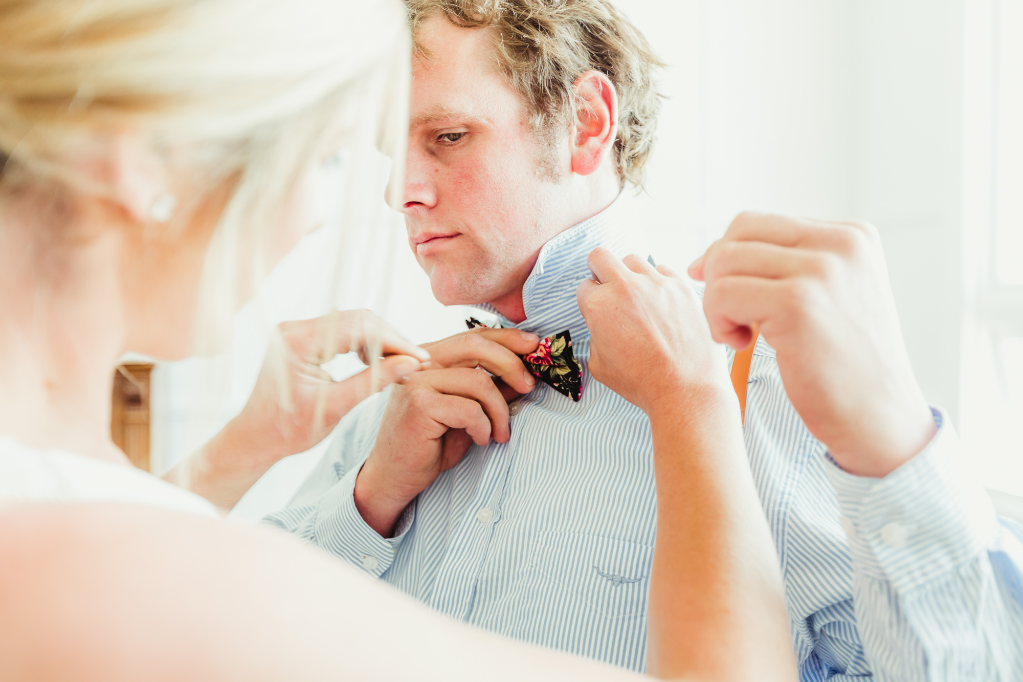 bride helping husband fix his floral bowtie for their otago elopement