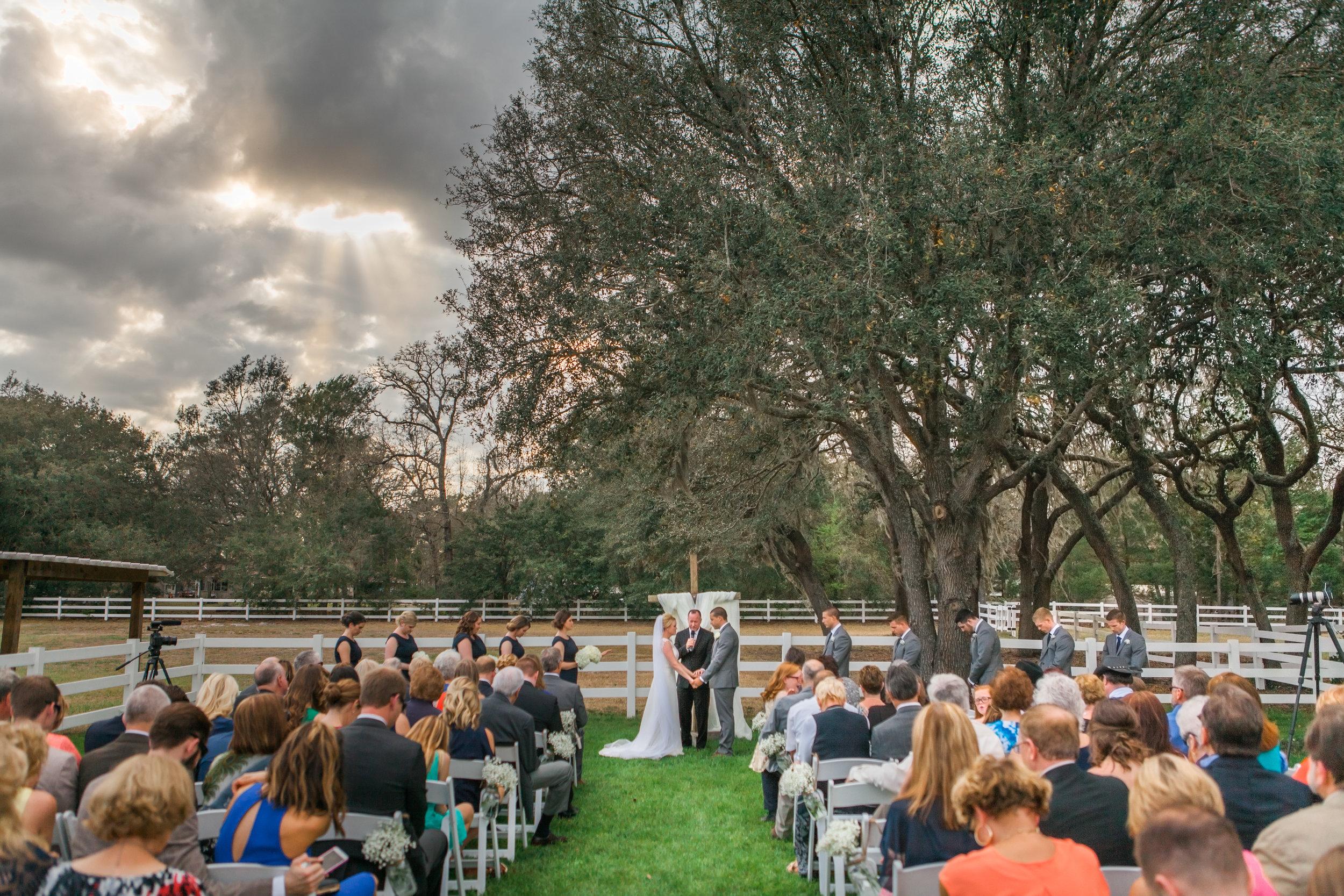 Sean & Claire's rustic Bramble Tree Estate wedding ceremony on the green lawn next to some lovely live oak trees.