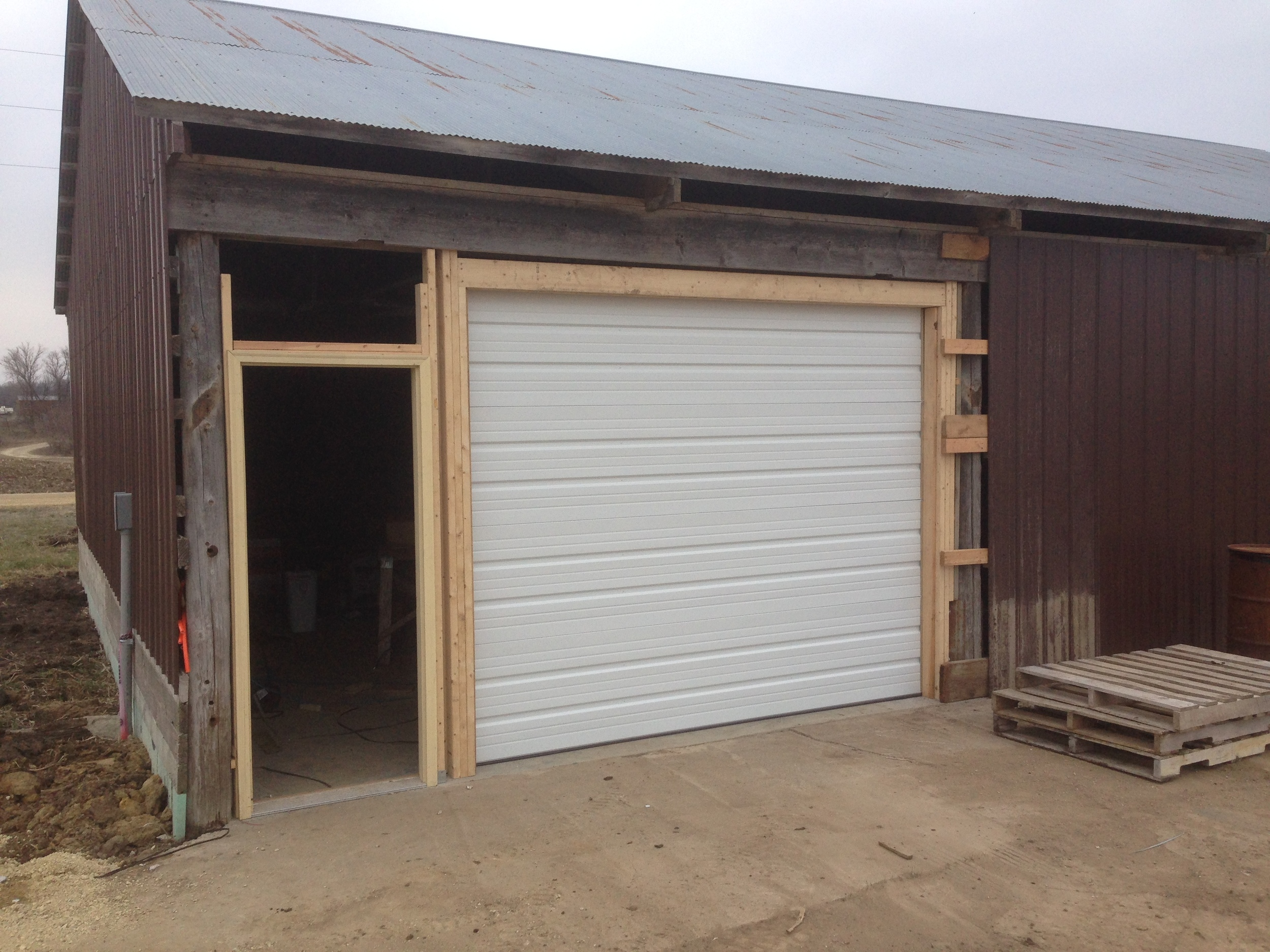 Overhead door is done and entry door frame in place. Next steps are to install the entry door and finish up the siding.
