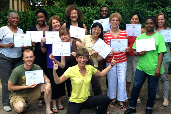 smiling group holding certified laugh yoga leader certificates