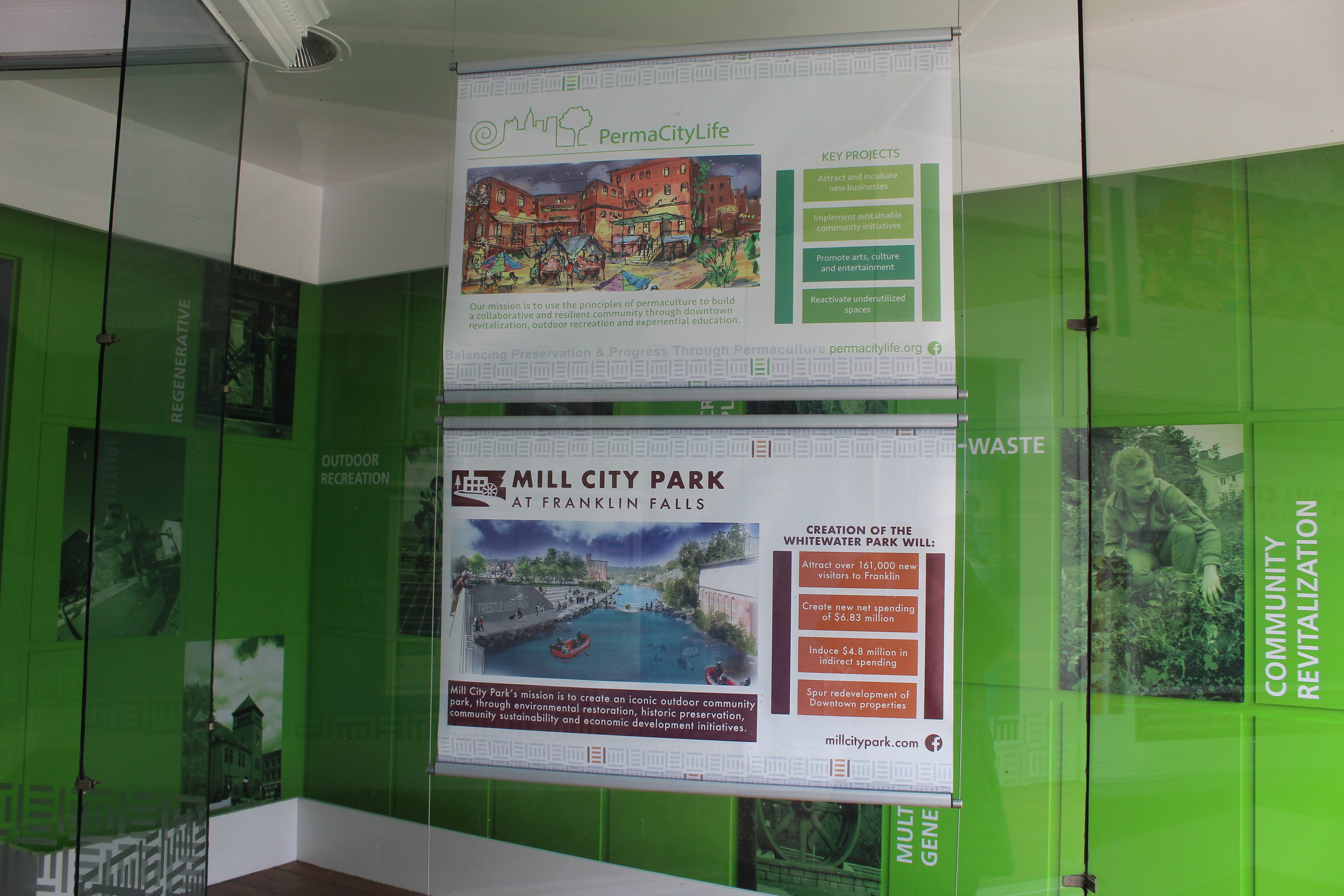 Melanie Patria's designs for advertising PermaCityLife and Mill City Park hanging in the SLI storefront (The Hub at 357 Central Street in downtown Franklin.