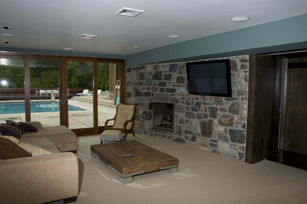 This entertainment room has the TV mounted directly to the stone wall behind it, and a full in-ceiling surround system make this an extraordinarily capable media room