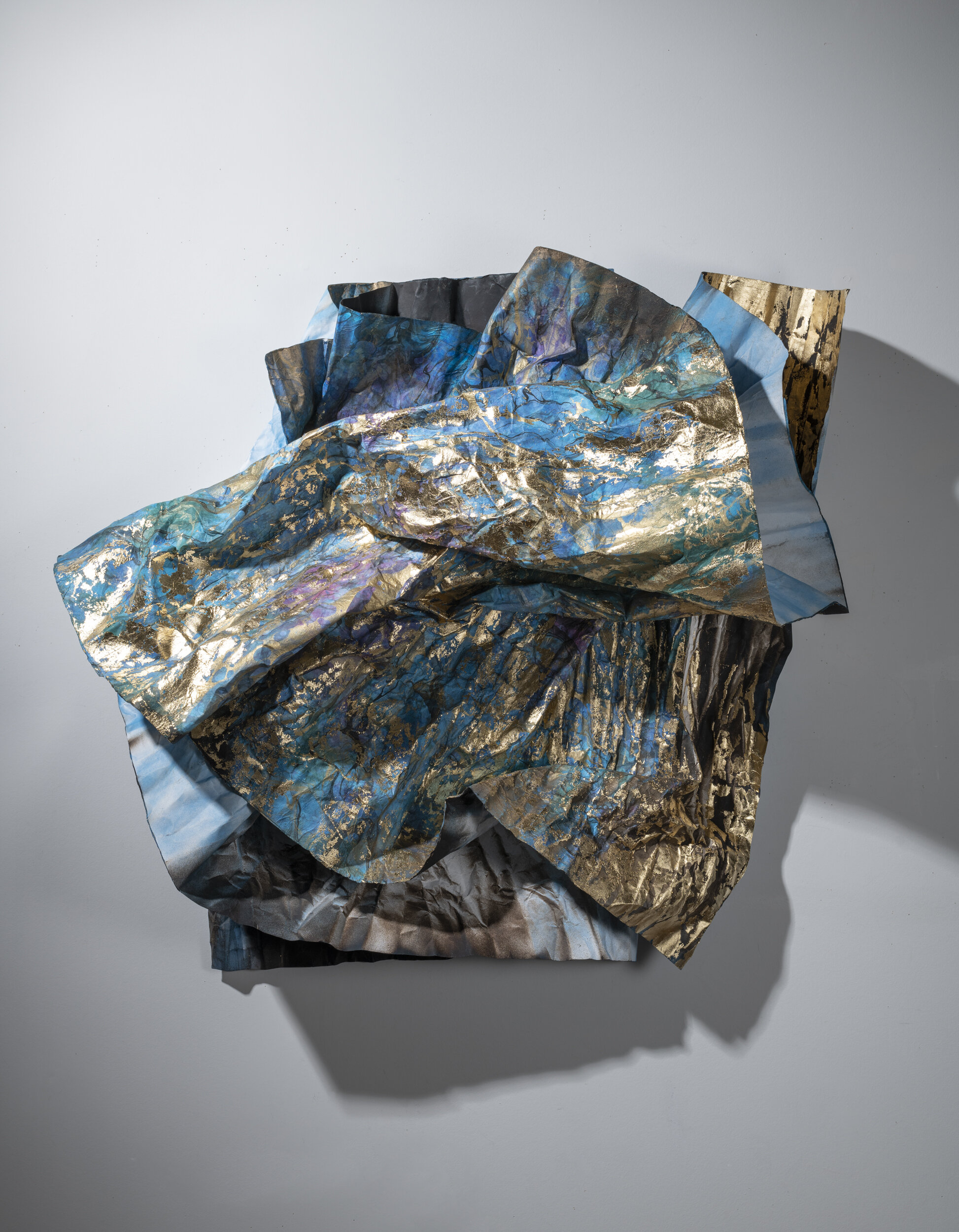 Damaged Emergency Blanket (for the Black and Blue Atlantic),  2018, 42 x 158 1⁄4 inches (with variable installation dimensions), composition gold leaf, acrylic spray paint and marbled paper collage on distressed paper