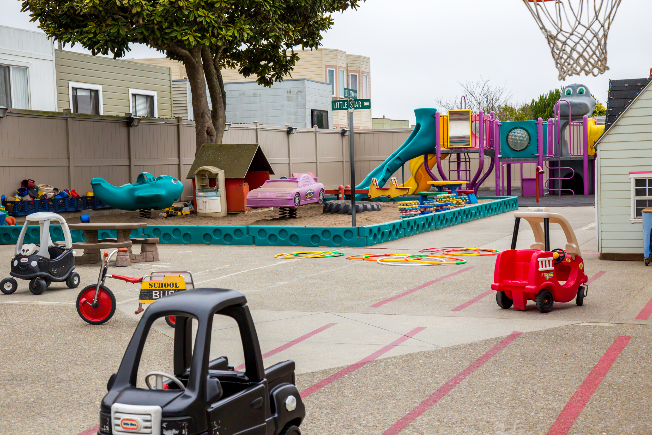 Other areas of our spacious yard include severalbasketball hoops of different heights, cars, bicycles, and scooters, and a large sandbox.