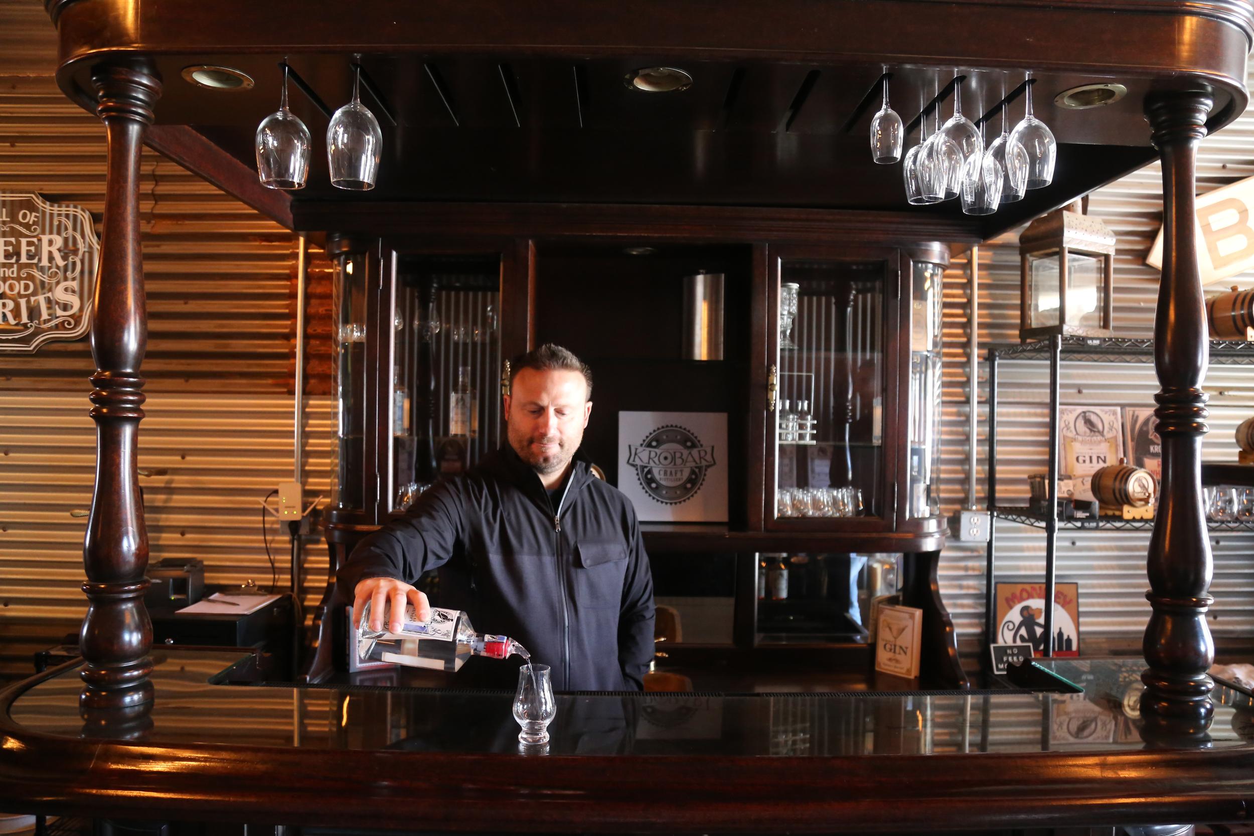 PHOTOS BY DYLAN HONEA-BAUMANN    KROBĀR Craft Distillery co-owner Stephen Kroener mans the tasting room, nestled behind Grey Wolf Wines.