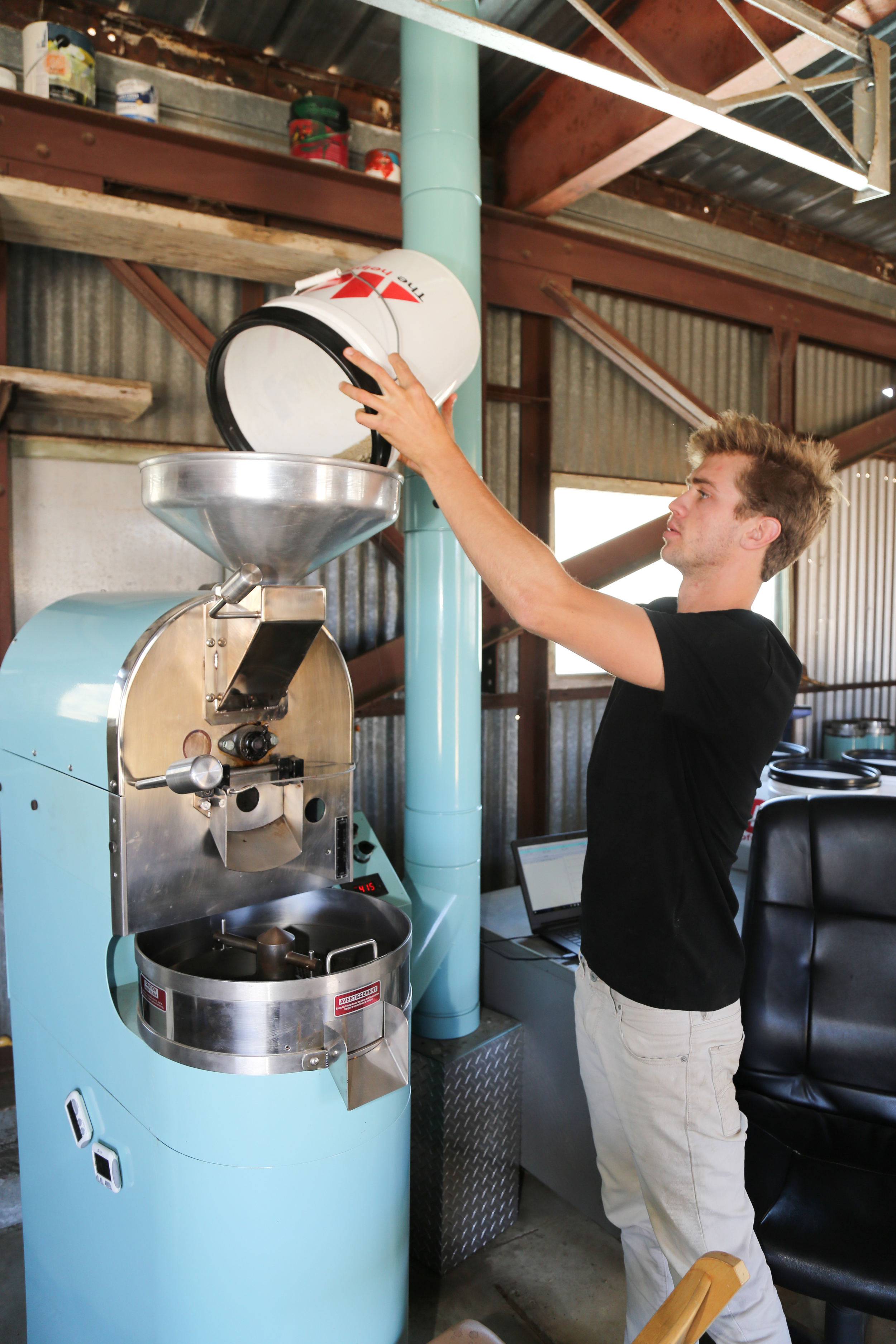 Paradigm Coffee co-founder and Roastmaster Reid Patterson roasts site-specific beans from Costa Rica with a state-of-the-art roaster he purchased from friend and fellow specialty coffee nerd Jonathan Strauf, owner of downtown coffee hub Bello Mundo.   PHOTO BY DYLAN HONNEA-BAUMANN