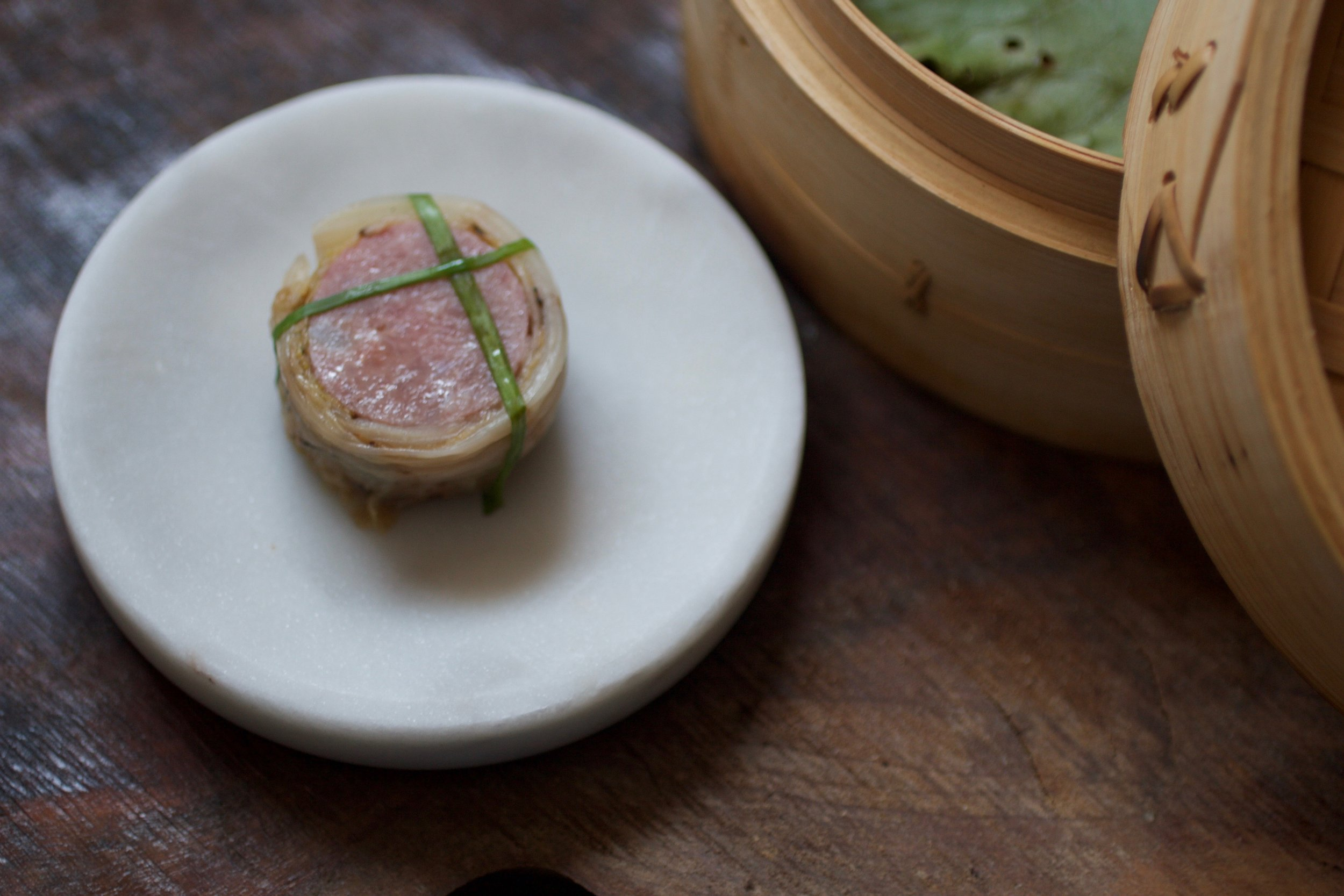 MANIACALLY CRAFTED   Pork and scallop sausage is served with carefully charred white kimchi.
